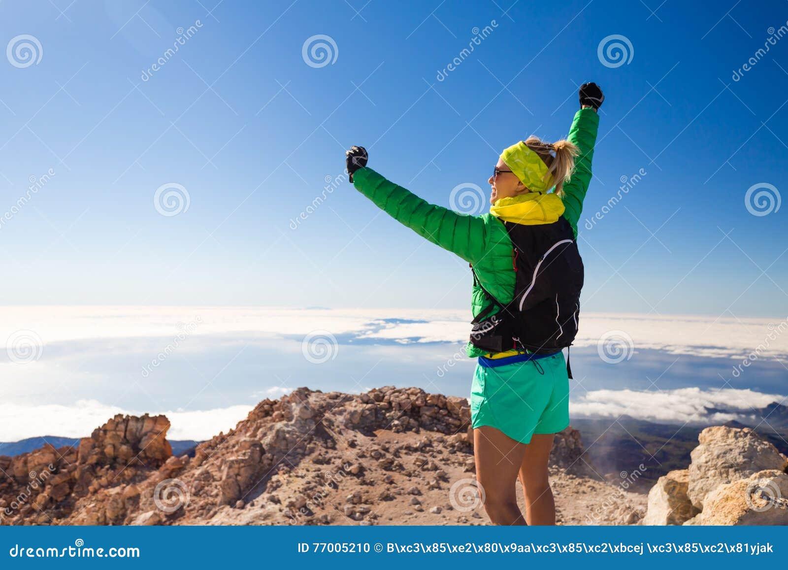 Caminhando a mulher que escala nas montanhas em Teide Tenerife
