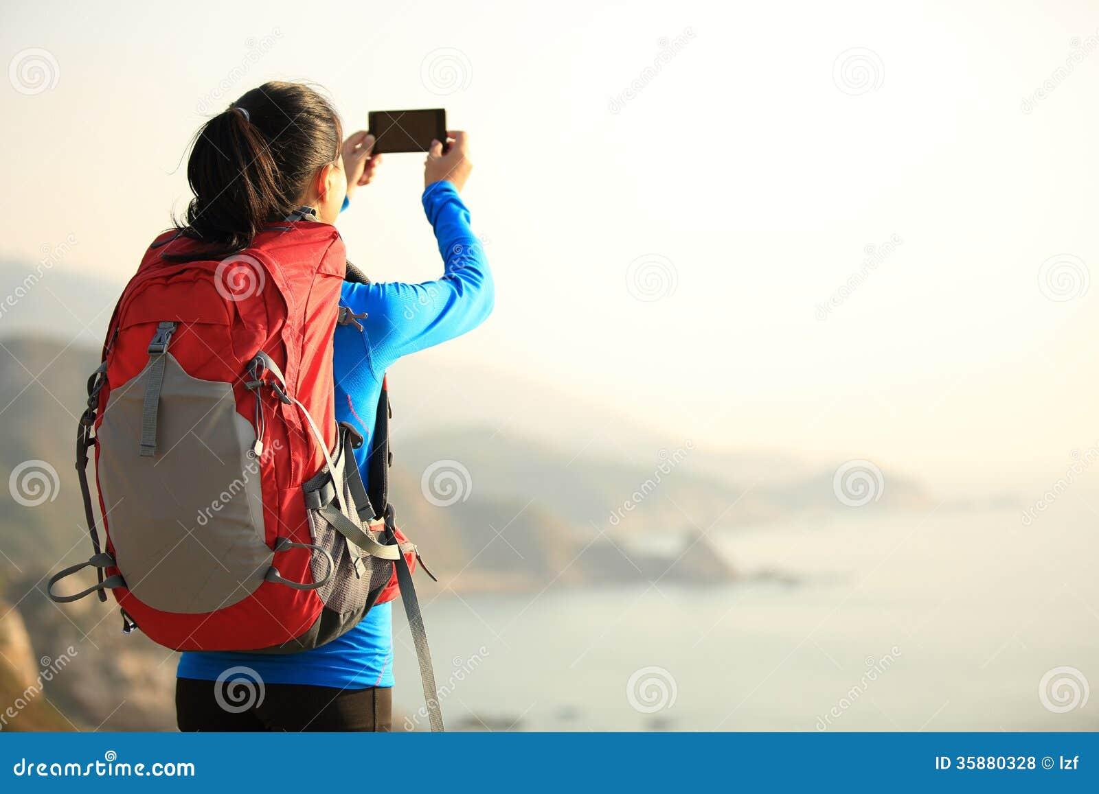 Caminhando o telefone esperto do uso da mulher que toma a foto