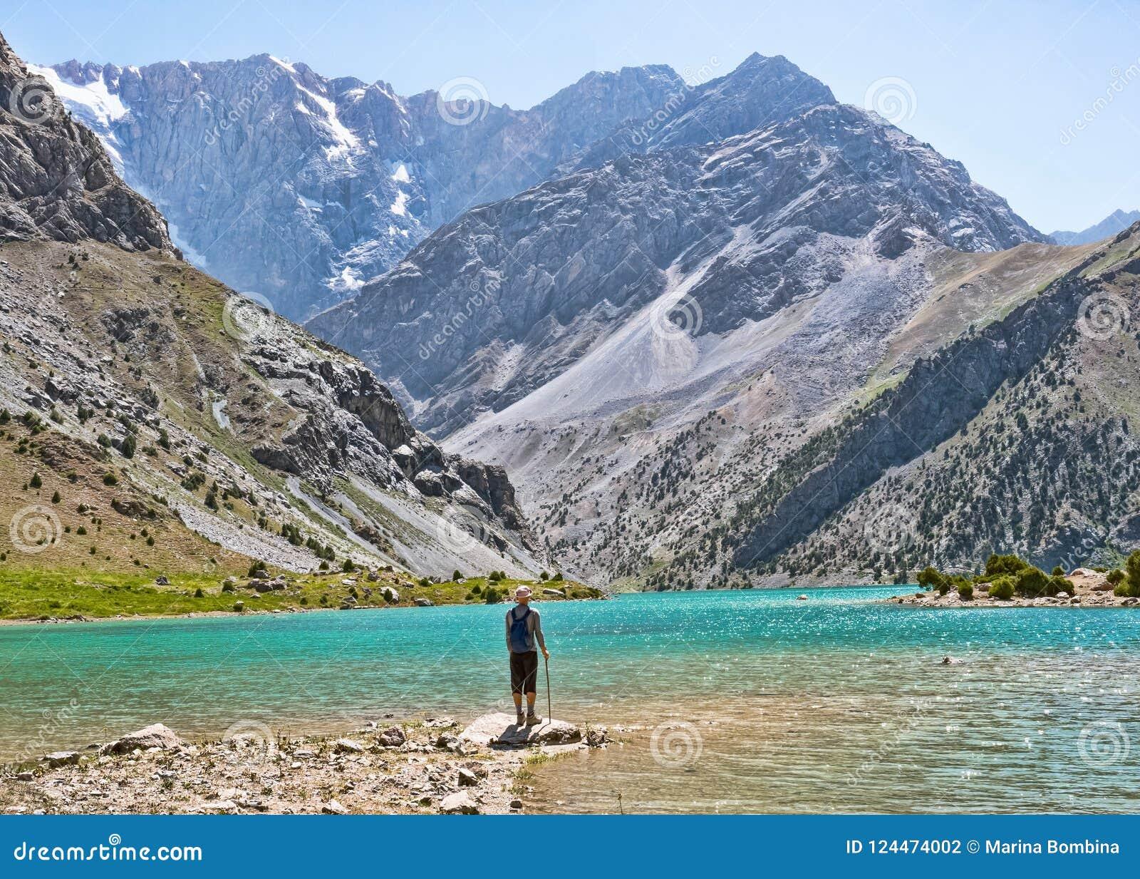 Caminhante com a trouxa perto do lago Kulikalon na montanha rochosa