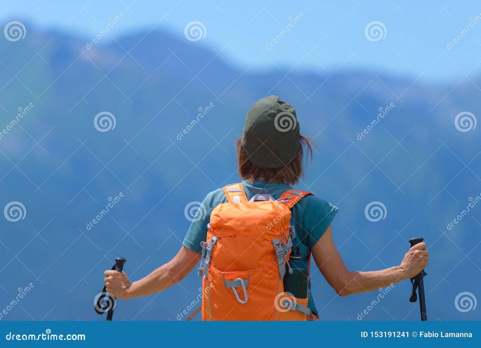 Caminhante da mulher na parte superior da montanha com trouxa e polos trekking, opinião traseira de foco seletivo, cumes no fundo