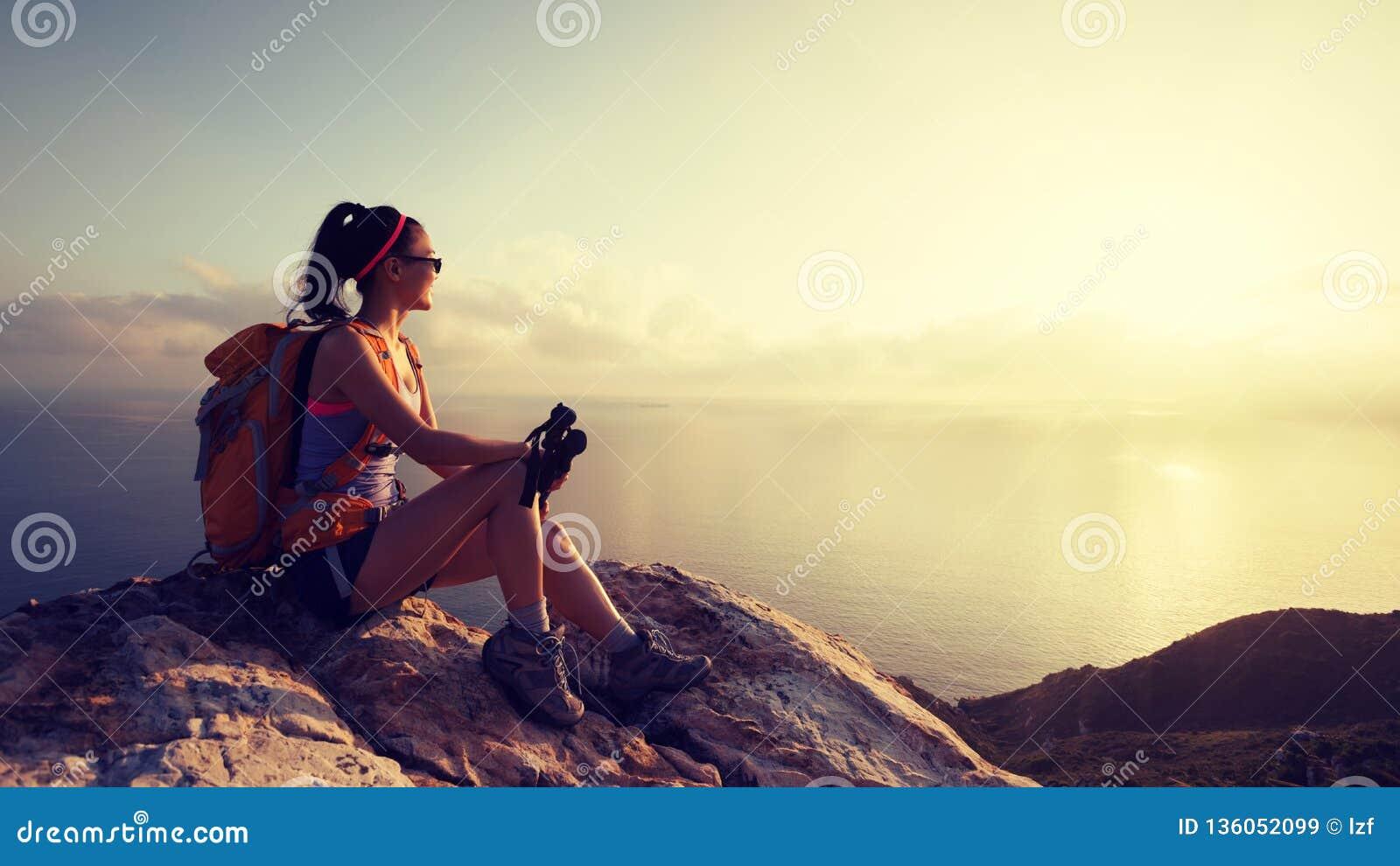 Caminhante da mulher no pico de montanha do beira-mar do nascer do sol