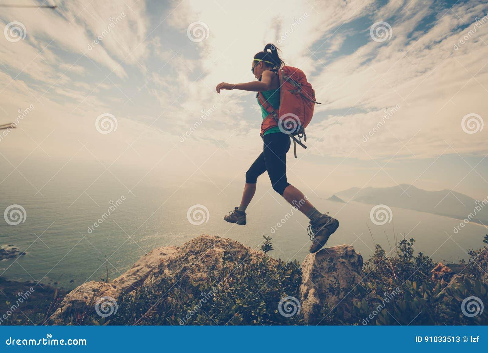 Caminhante da mulher que caminha no pico de montanha