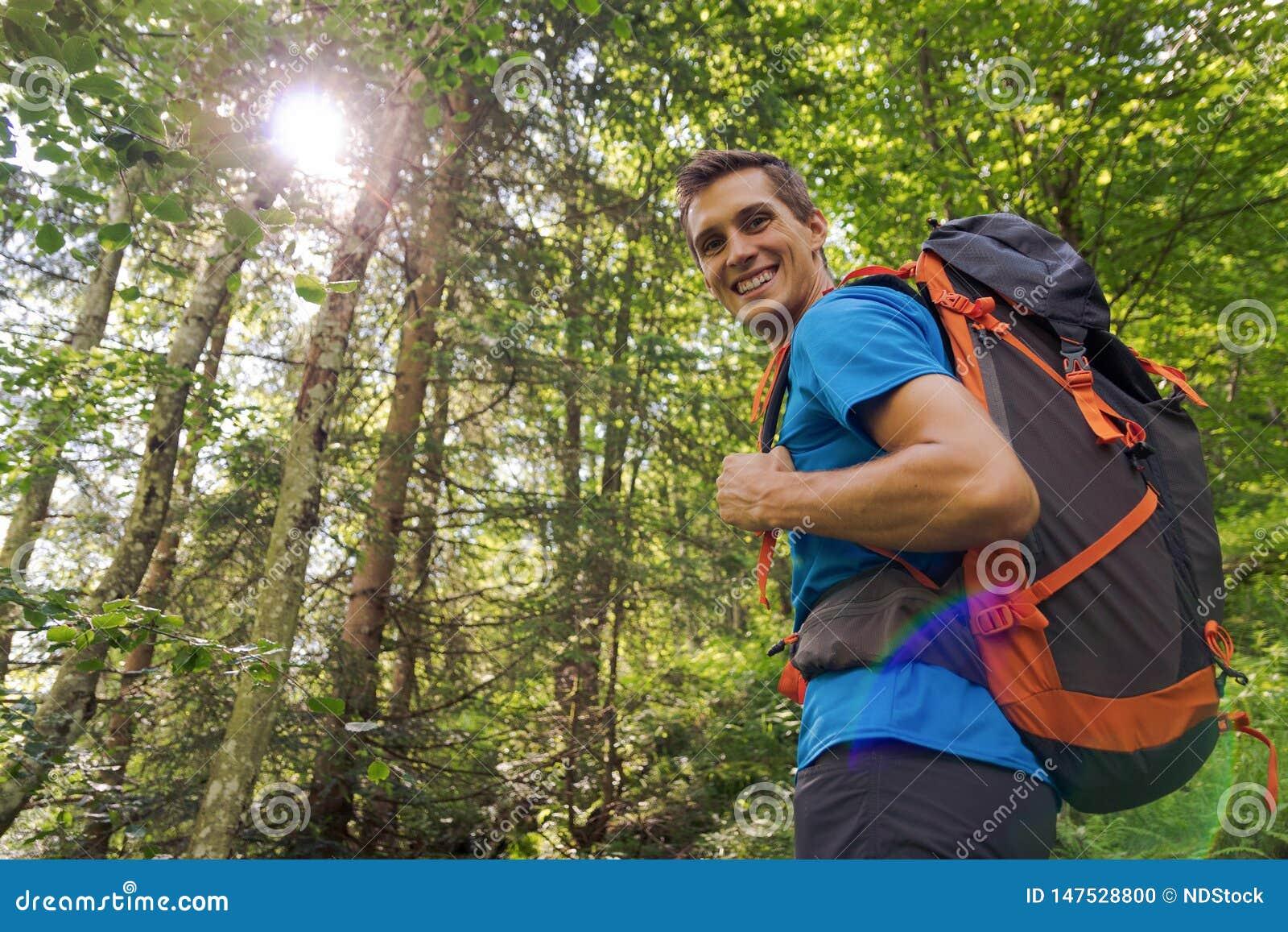 Caminhante masculino com trouxa grande que sorri à câmera cercada por árvores e por luz solar
