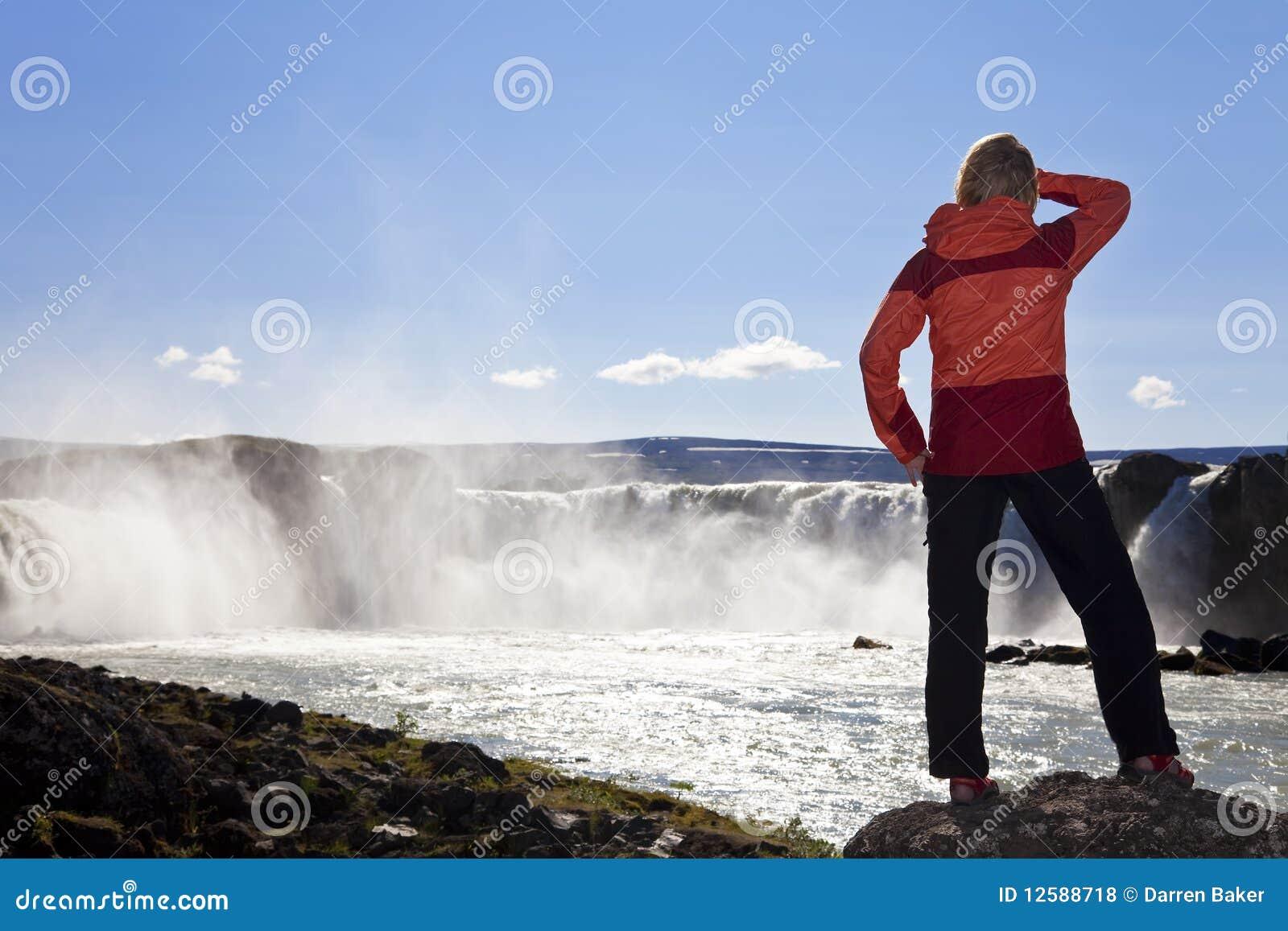 Caminhante que está em uma cachoeira, Islândia da mulher