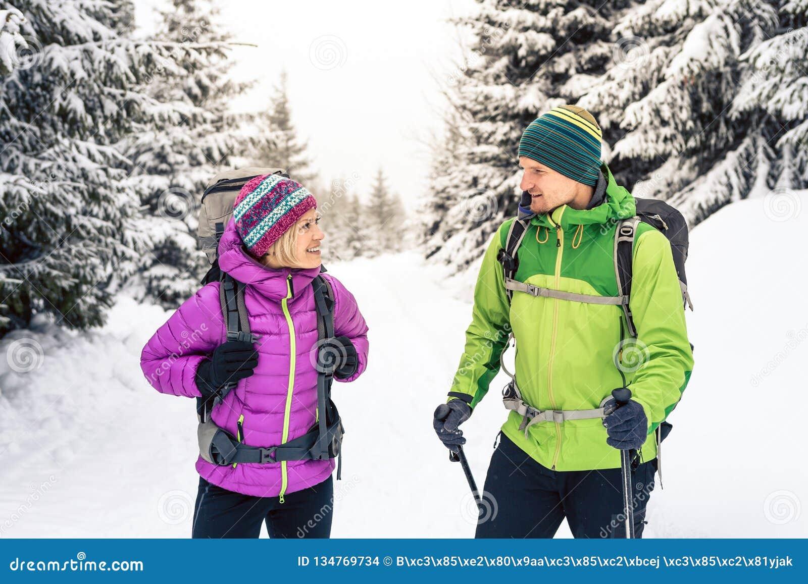 Caminhantes dos pares que trekking em madeiras do inverno