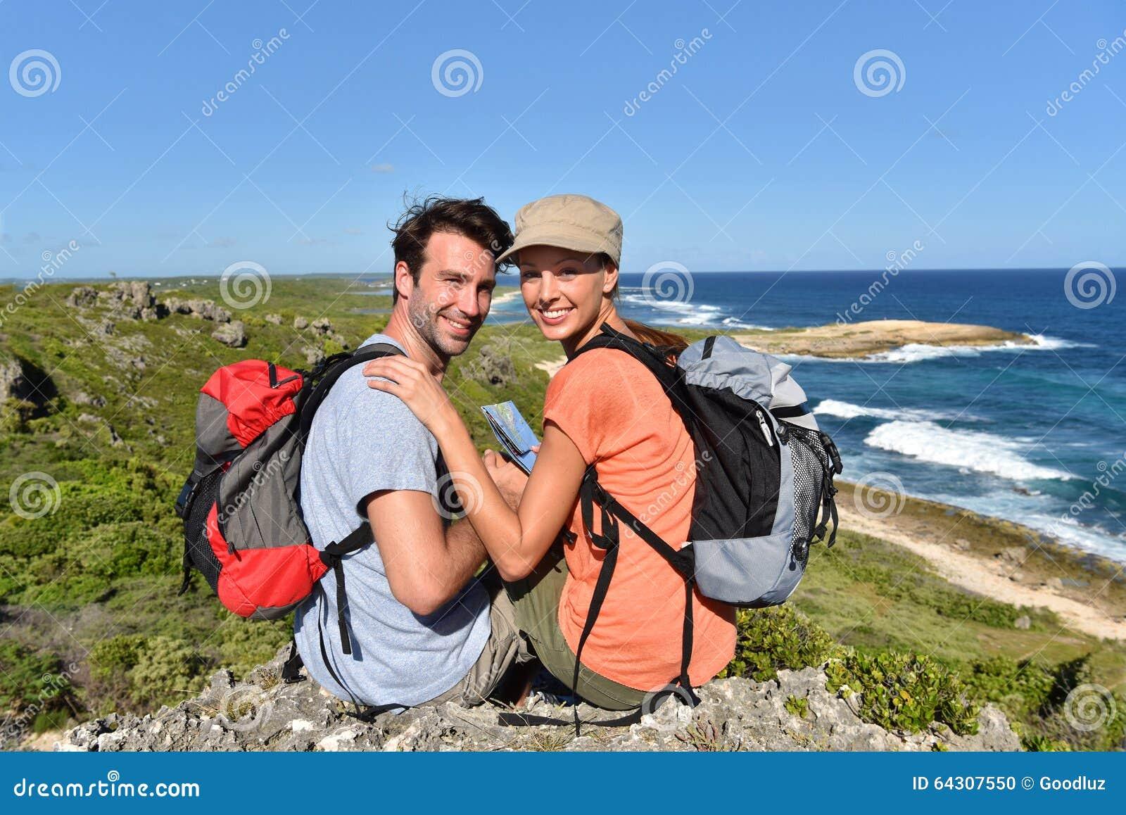 Caminhantes na viagem que apreciam a vista em ilhas