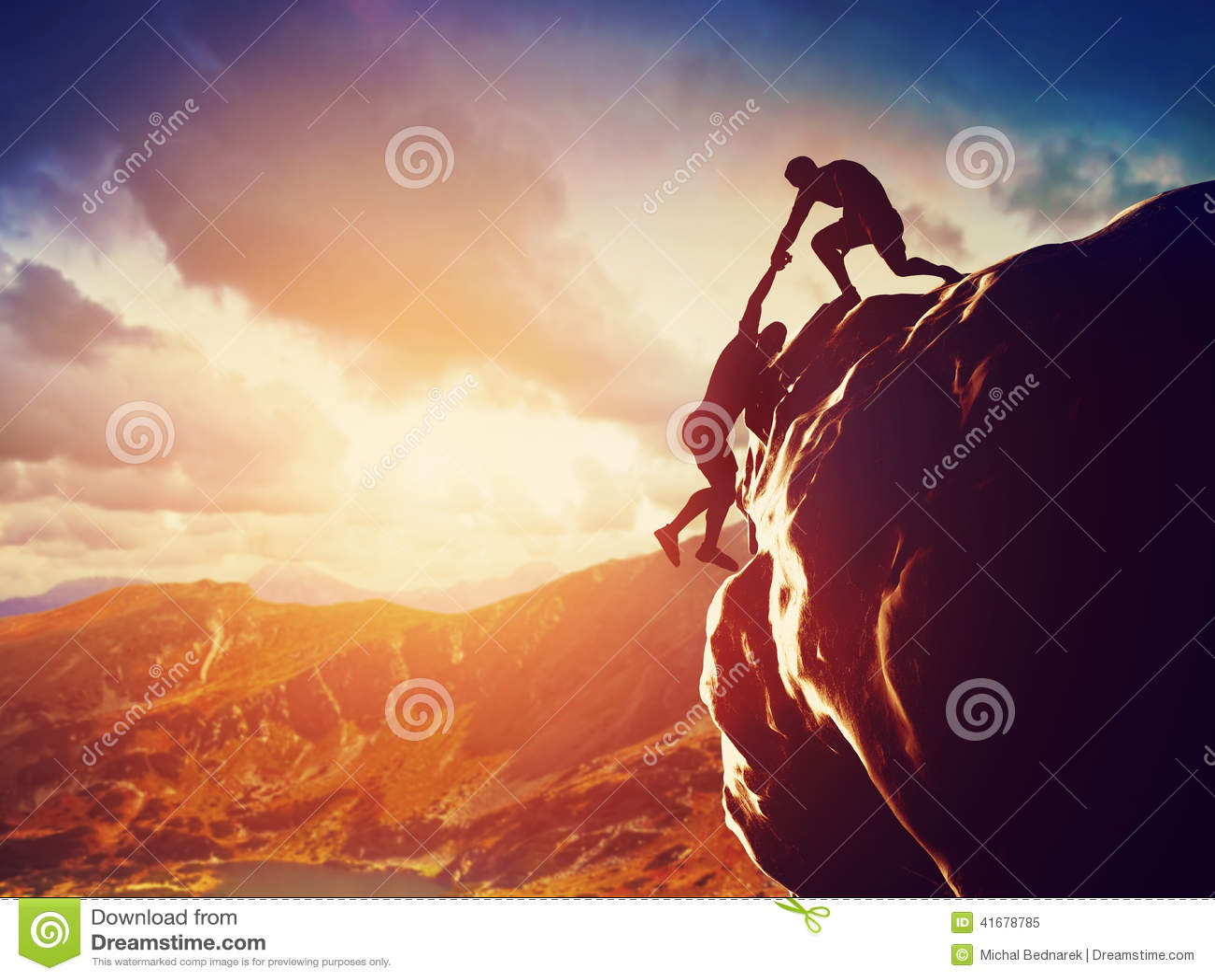 Caminhantes que escalam na rocha, dando a mão e ajudando a escalar