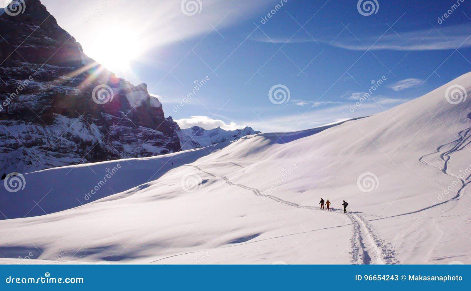Caminhantes que snowshoeing no pé da cara norte de Eiger nos cumes suíços perto de Grindelwald