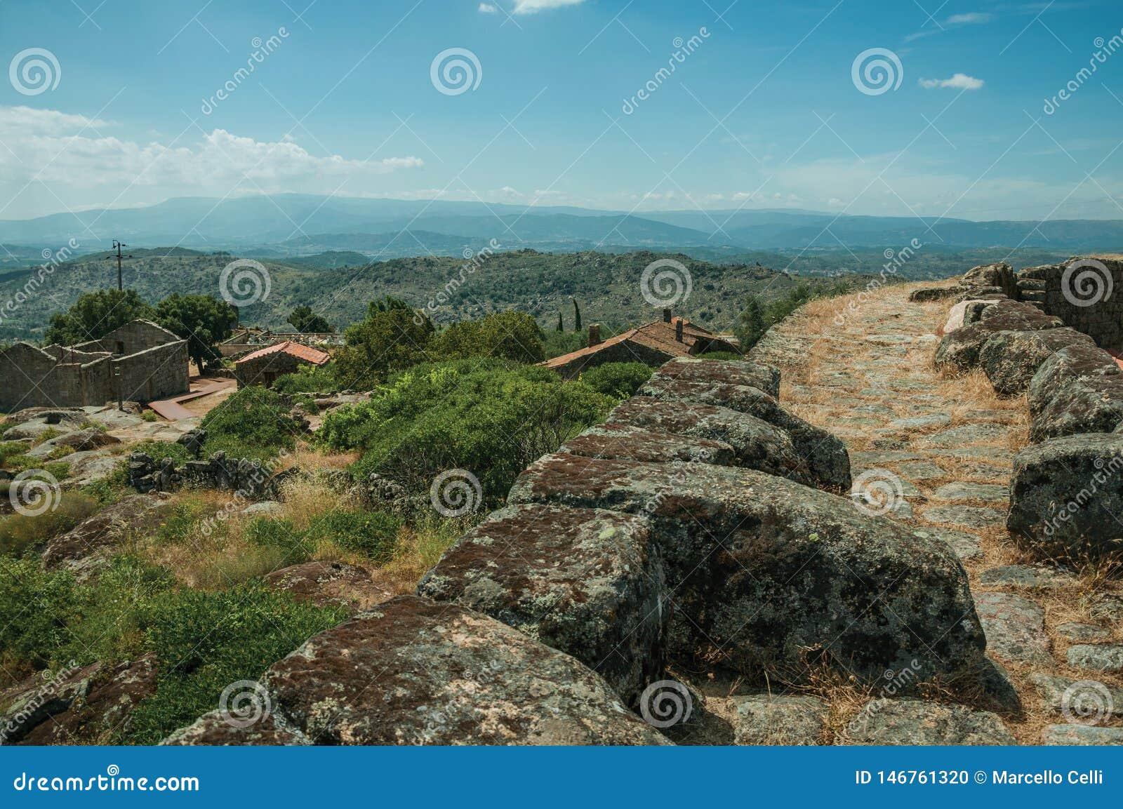 Caminho sobre a parede de pedra ao lado das casas velhas