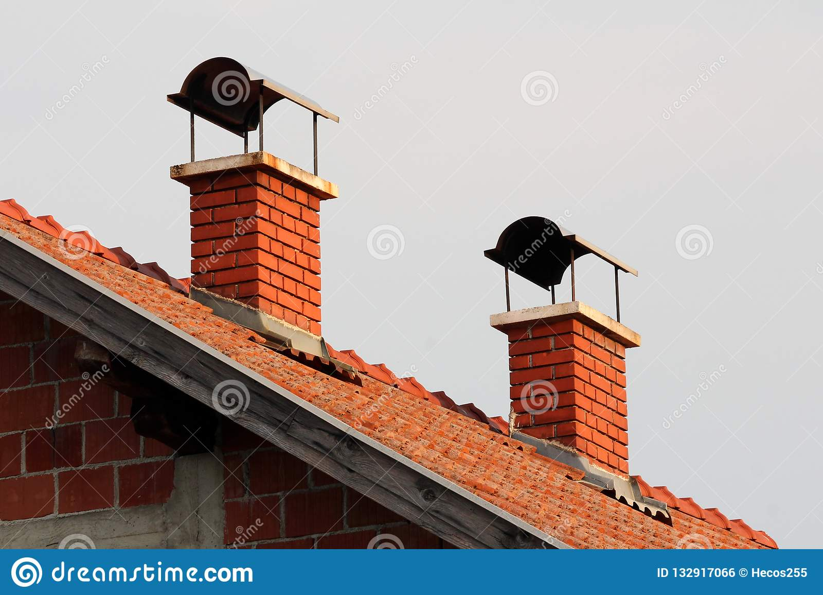 Camini del mattone rosso con protezione del metallo sulla cima sulla casa suburbana non finita della famiglia al tramonto