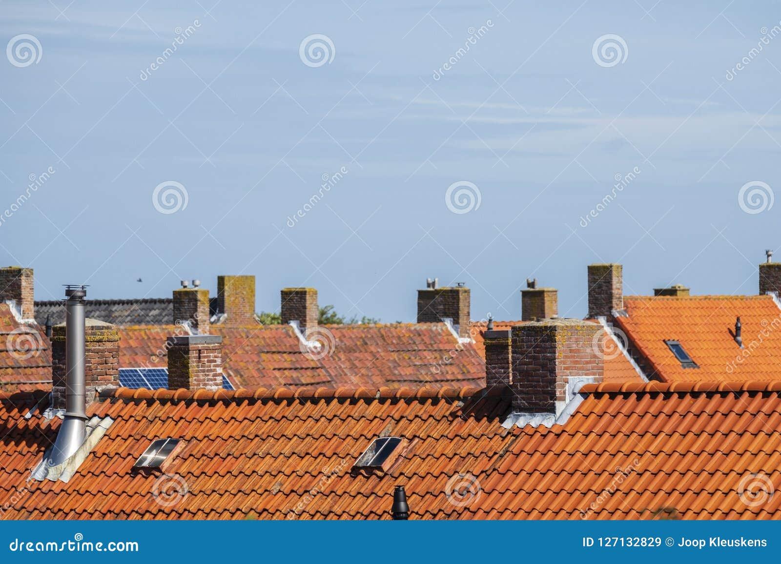 Immagini Camini In Pietra camini di pietra sui tetti con le mattonelle di tetto