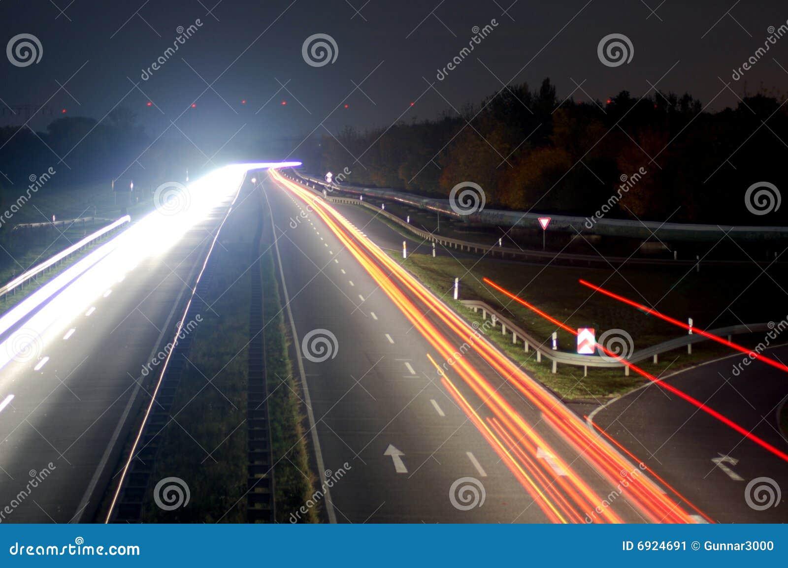 Camino con tráfico de coche en la noche con las luces borrosas