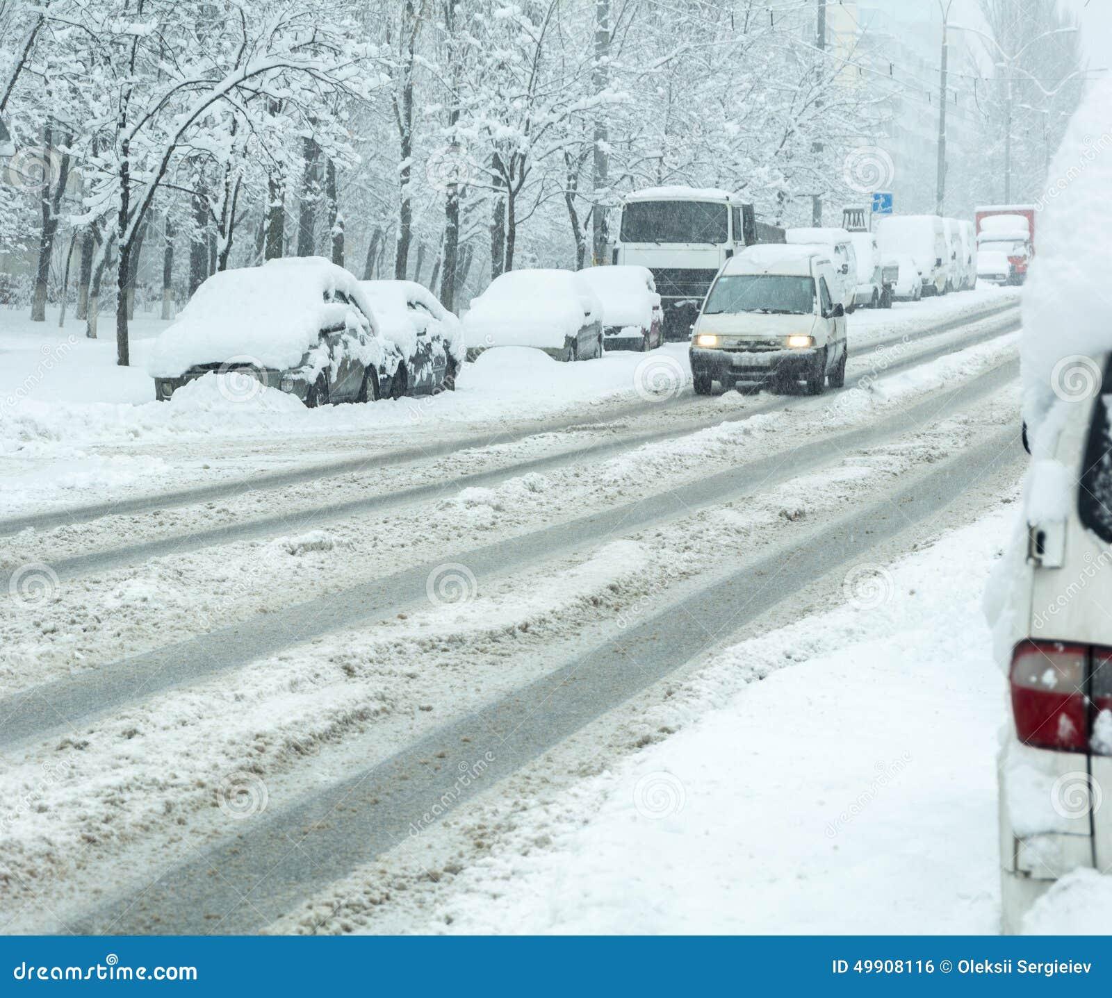 Camino del invierno Nevado con los coches en tormenta de la nieve