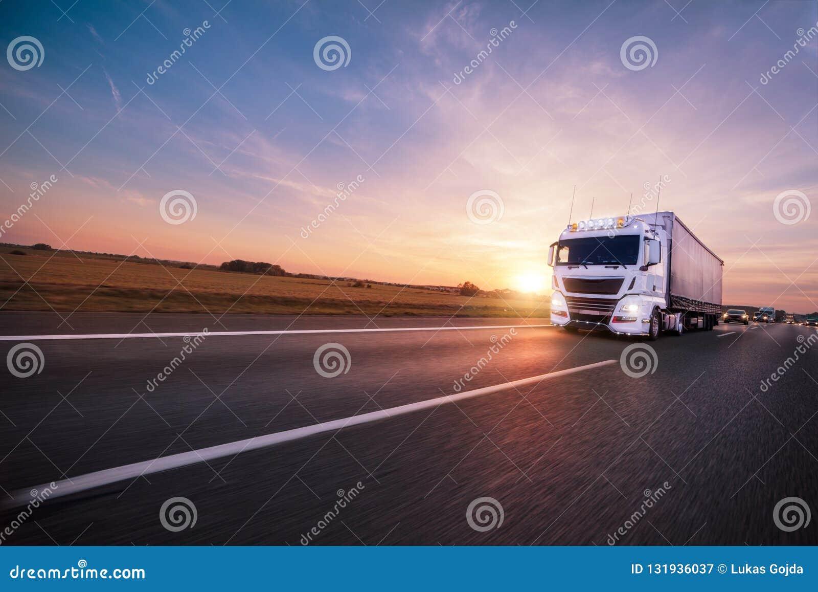 Camion con il contenitore sulla strada, concetto del trasporto del carico
