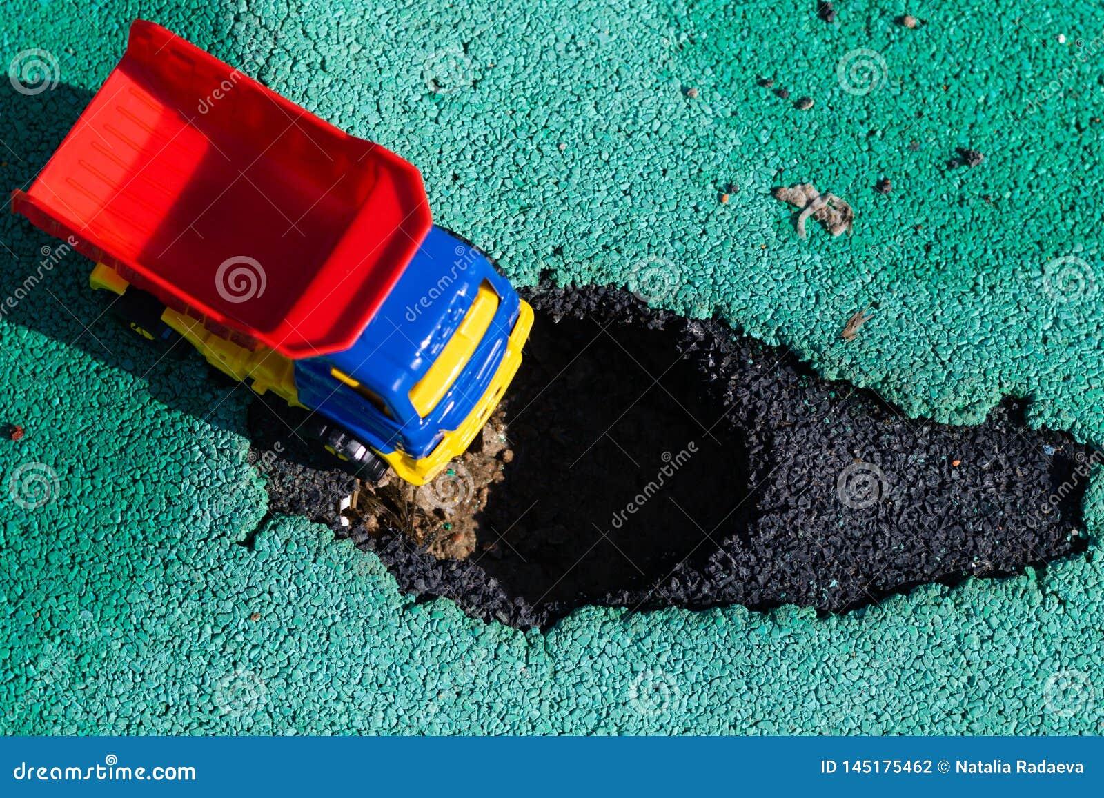 Camion en plastique de jouet avec un corps rouge arrêté devant le puits La voiture ne peut pas disparaître Trou sur l asphalte