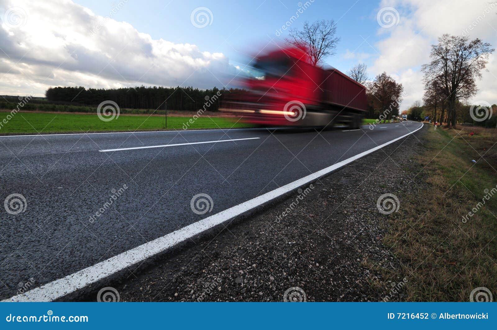 Camion rouge dans un mouvement sur la route de macadam
