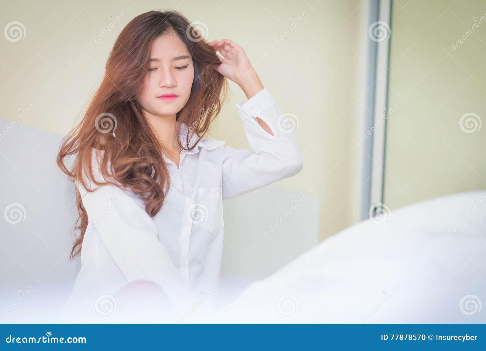 Camisa Blanca Que Lleva De La Mujer Hermosa Elegante Que Presenta En Dormitorio, Foto de archivo