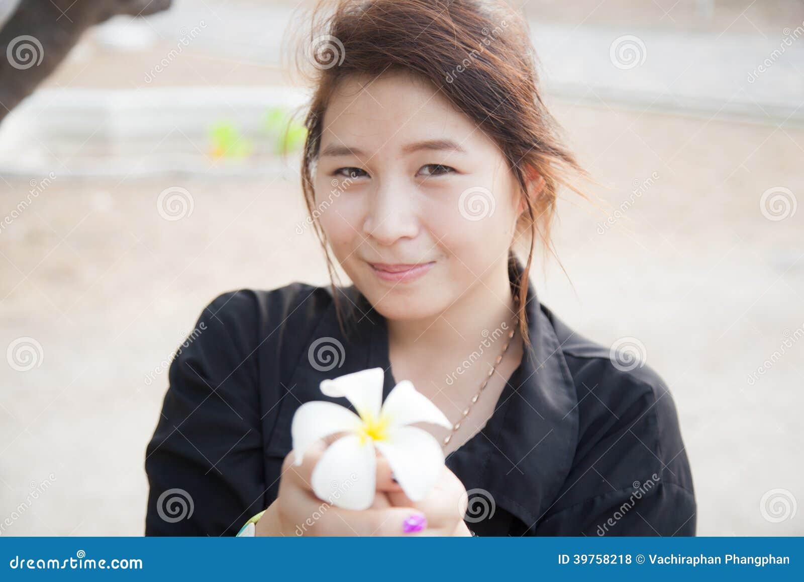 a52f5485f56e2 Camisa asiática del negro de la mujer. Llevar a cabo flores blancas y un  soporte de flor.