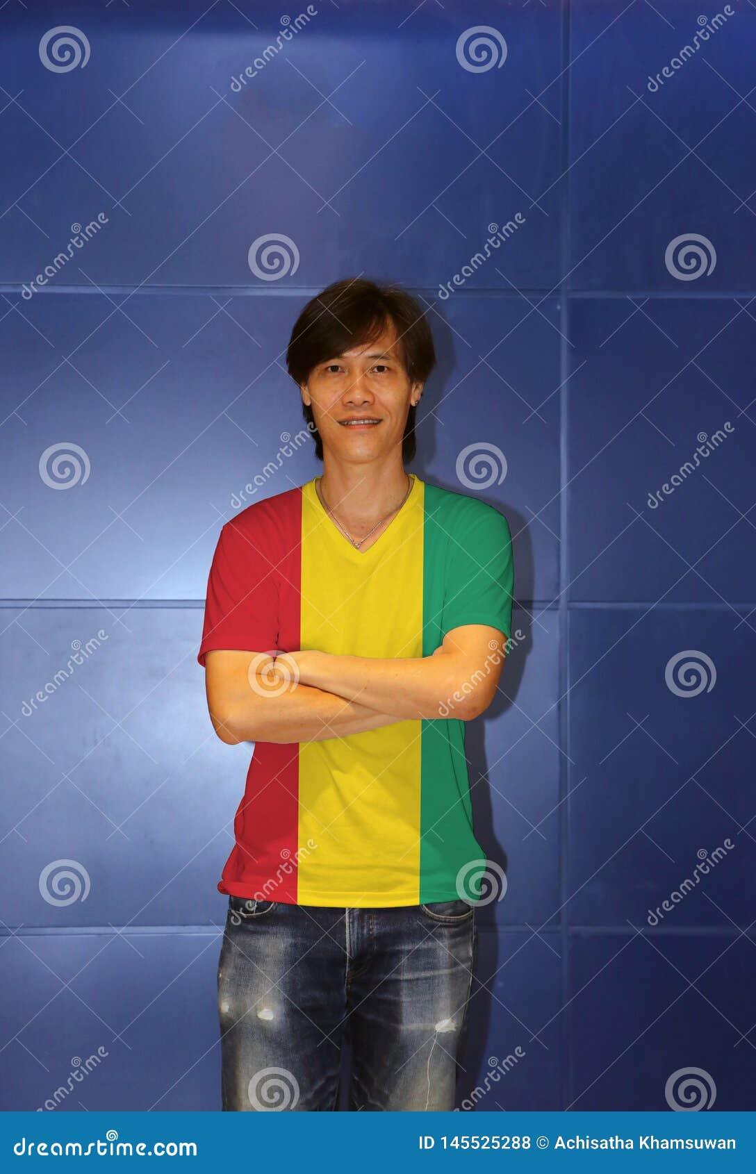Camisa vestindo do teste padr?o da bandeira da Guin? do homem e para cruzar seu bra?o no fundo azul da parede