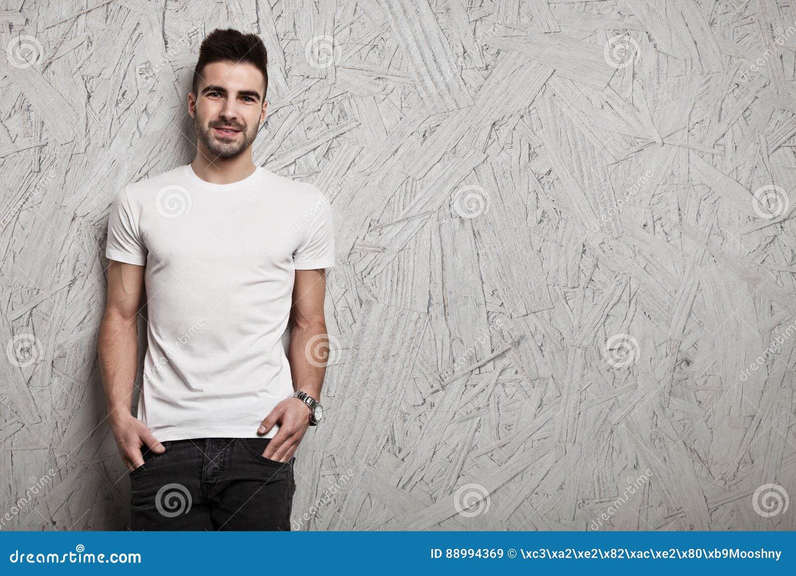 eeeb922d8 Hombre sonriente en la camiseta en blanco blanca, y fondo de madera de la  pared de OSB