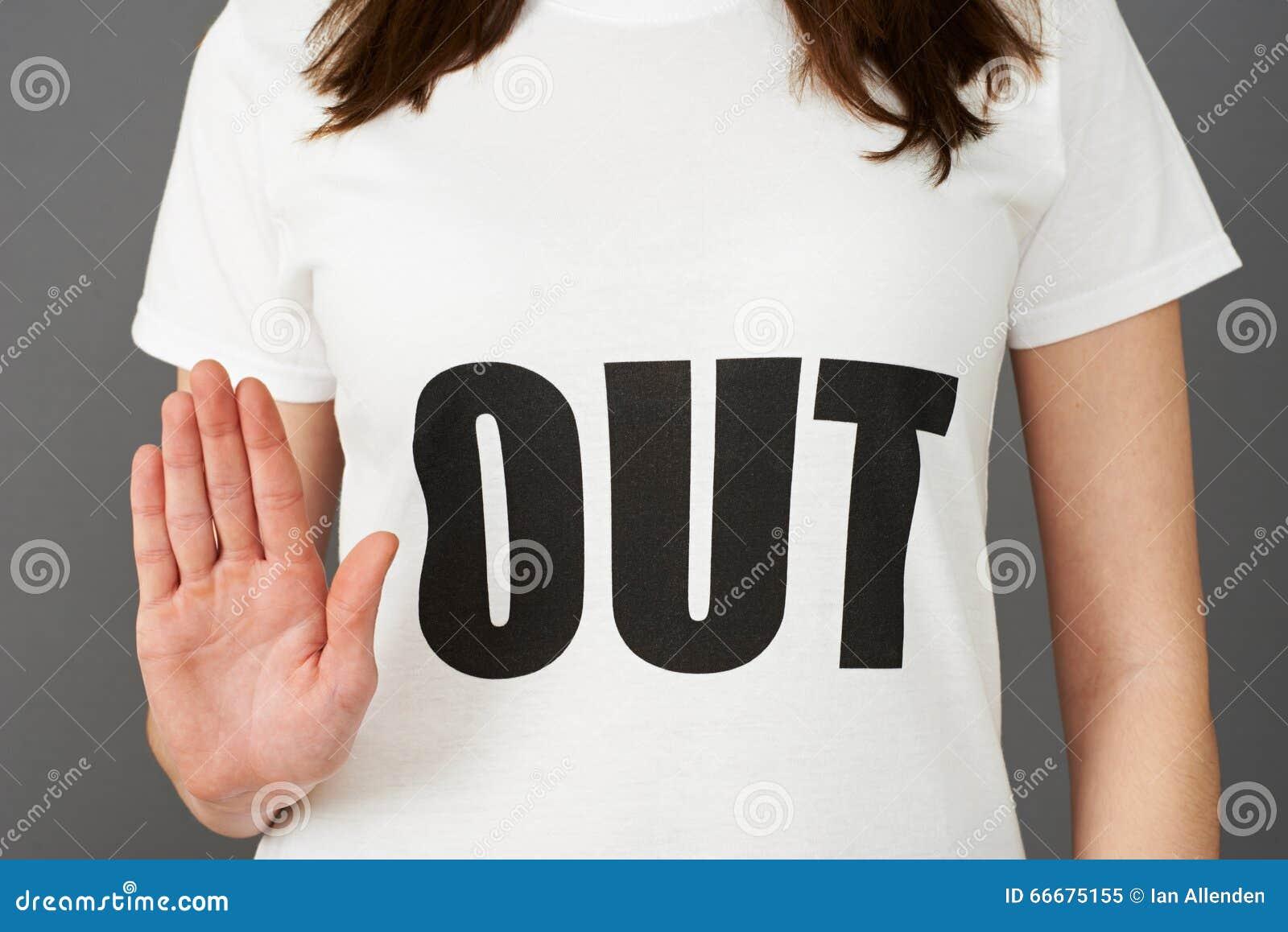 Camiseta que lleva del partidario de la mujer joven impresa con HACIA FUERA lema