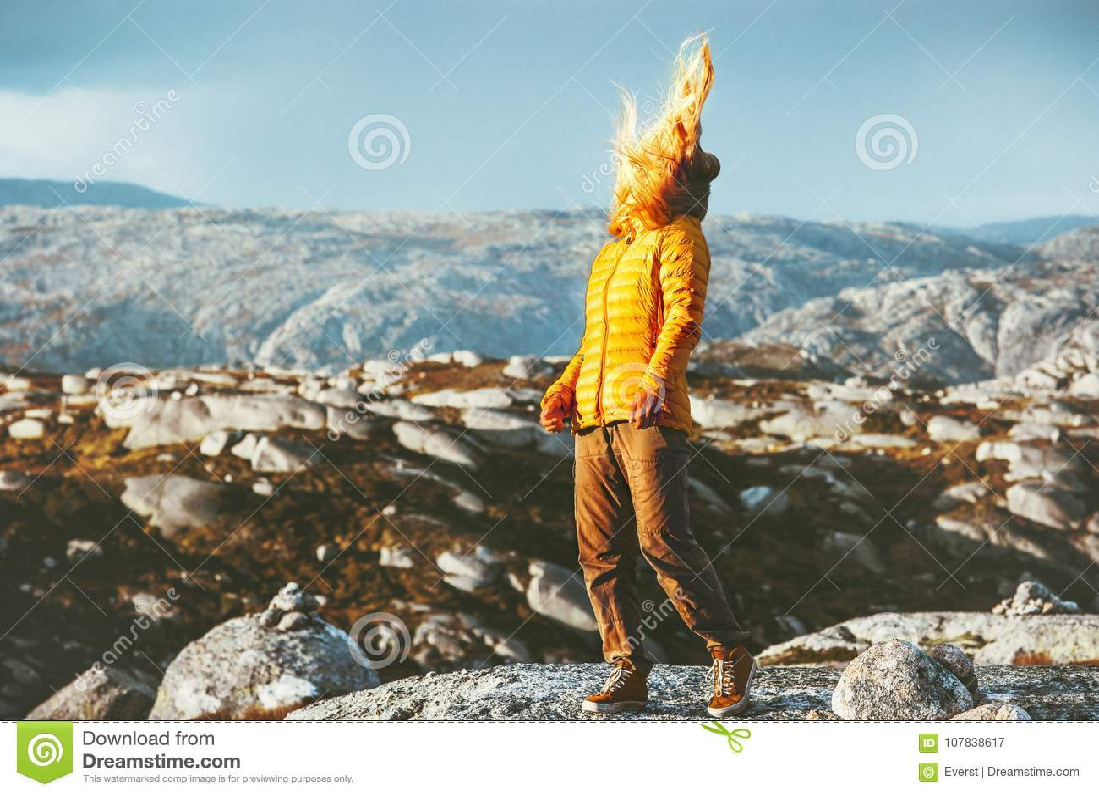 Camminata bionda della donna all aperto in capelli delle montagne su vento