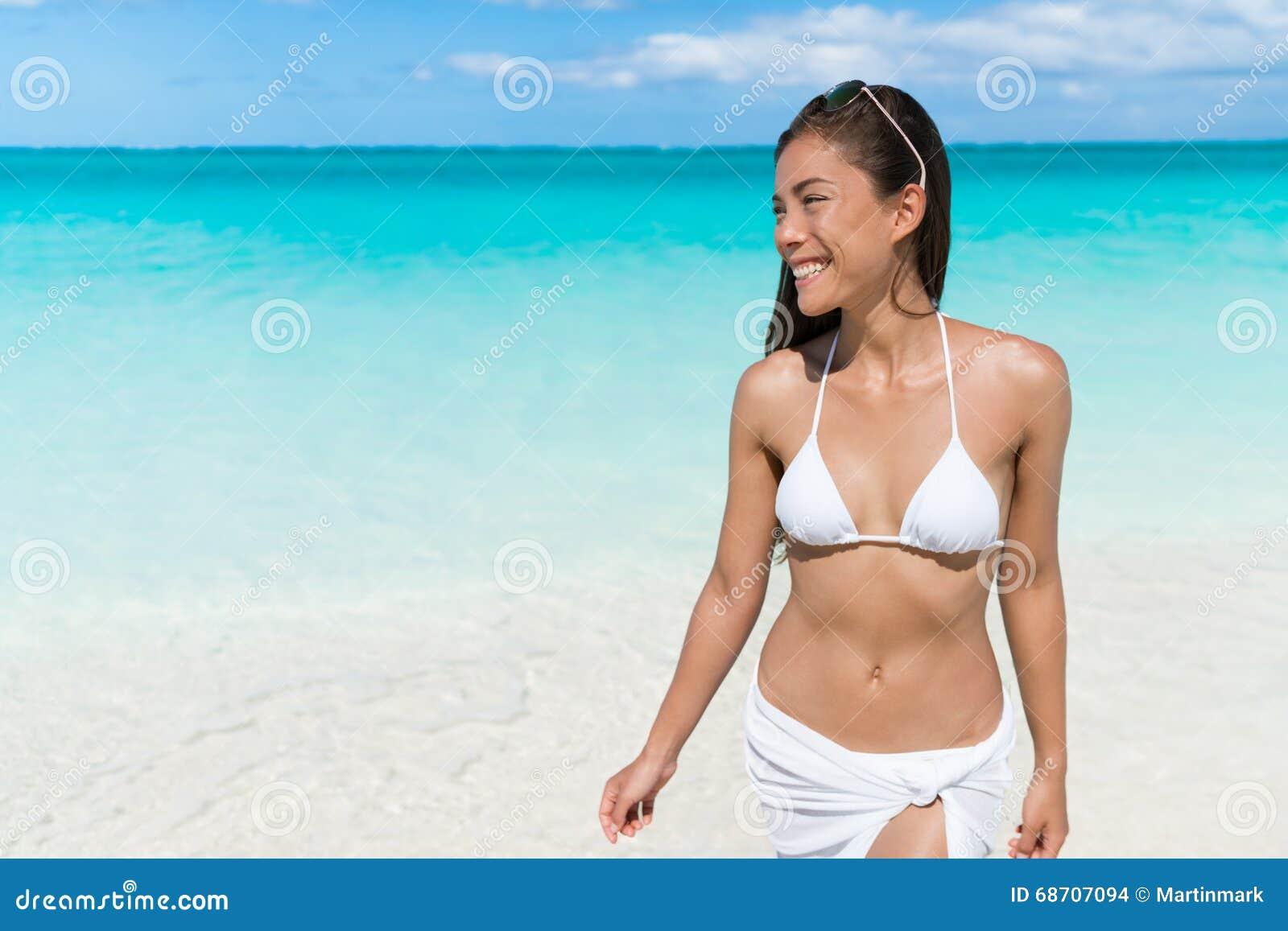 Camminata di rilassamento della donna asiatica del bikini sulla spiaggia bianca