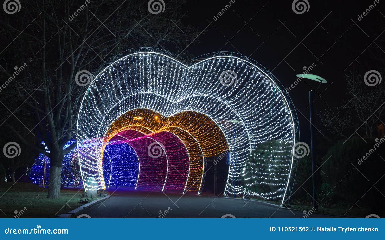 Cammini dal tunnel leggero della ghirlanda in una città alla notte