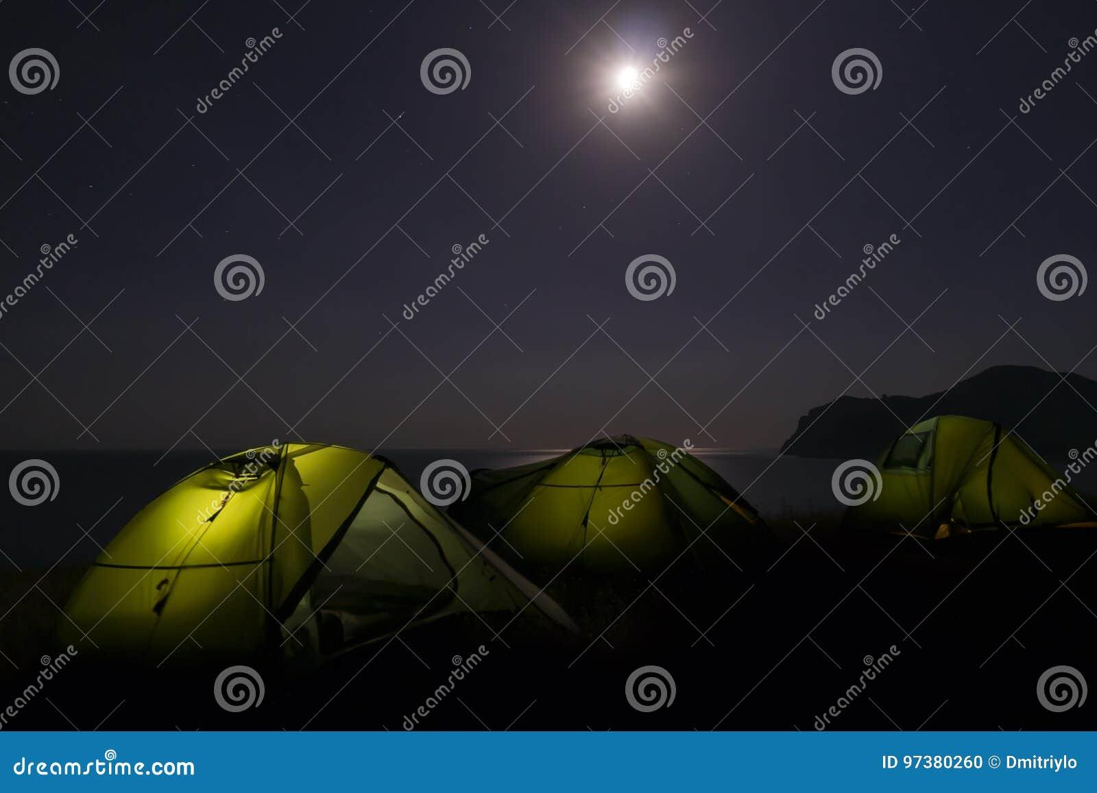 Camp de tentes de trekking avec la lumière de lampes-torches à l intérieur sous le ciel nocturne foncé et la pleine lune Équipeme