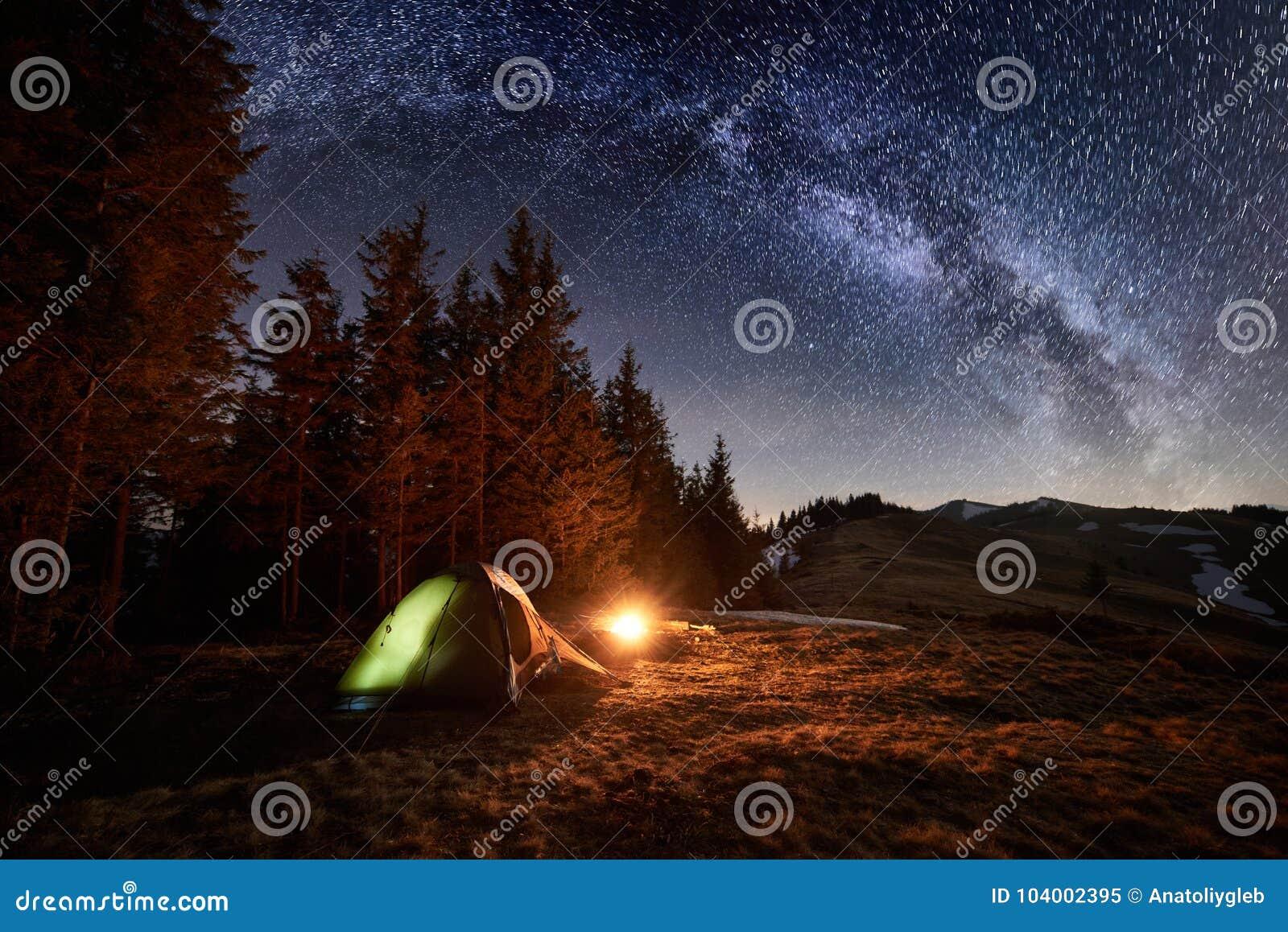 Campa för natt Upplyst tält och lägereld nära skog under natthimmel mycket av stjärnor och den mjölkaktiga vägen