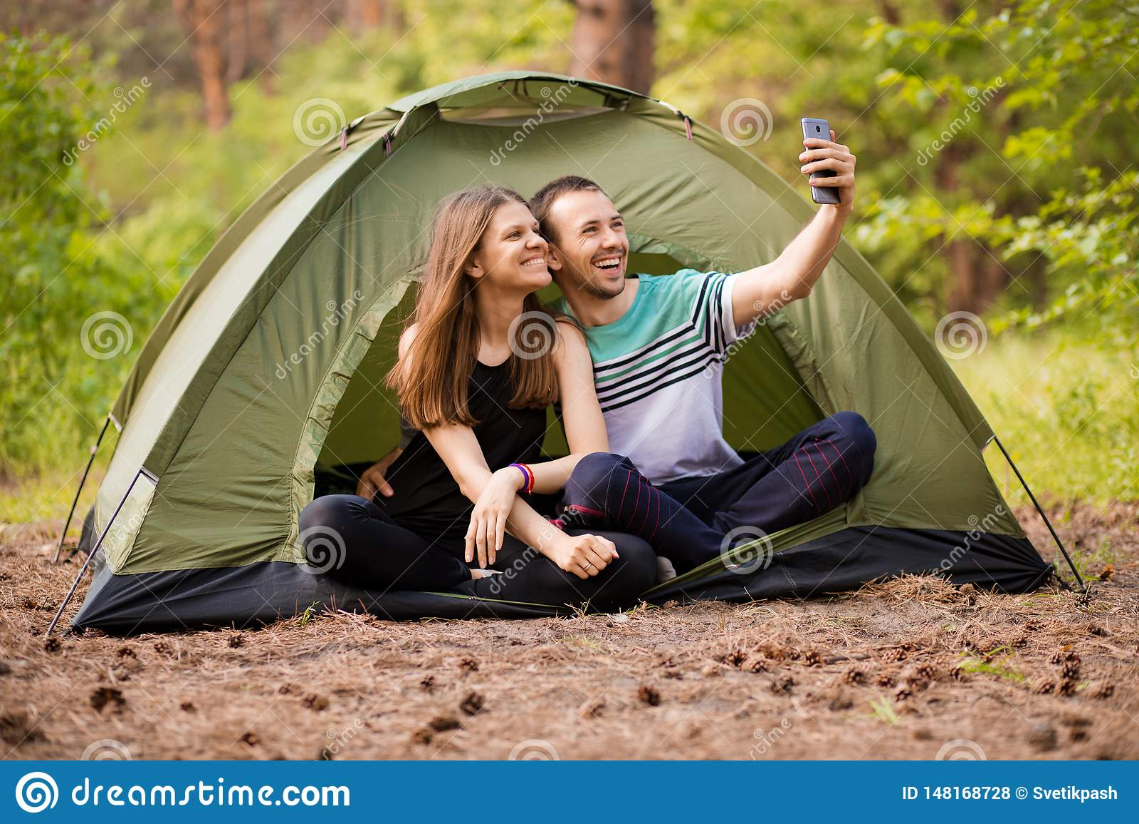 Campa par i tältet som tar selfie Lyckliga vänner som har rolig togheter Begreppslivsstil och teknologi