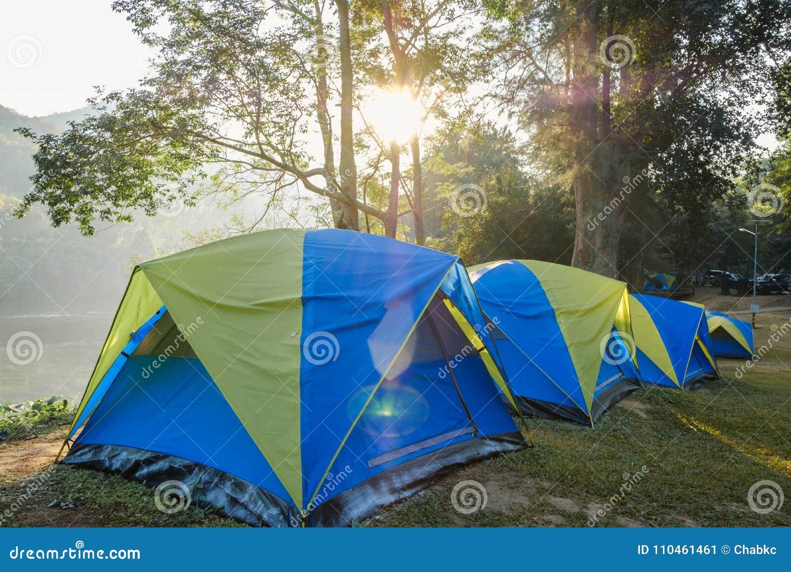 Campa tält i gräsmattan med solljusmorgon