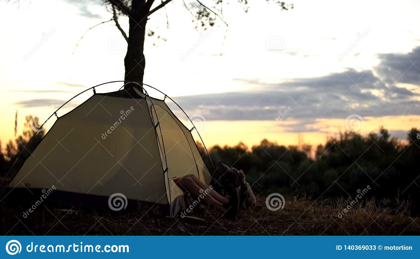 Camper resting in tent early in picturesque place, overnight in wild, sunrise