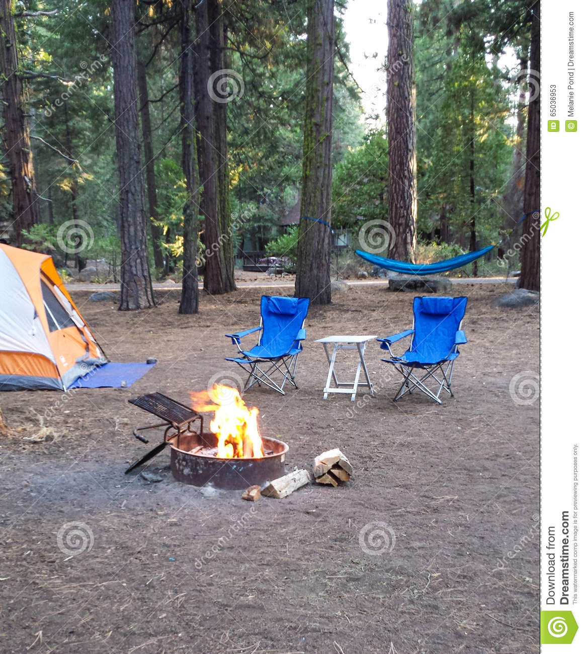 Download Campsite In The Woods With A Tent,two Chairs, Hammock And A Burning