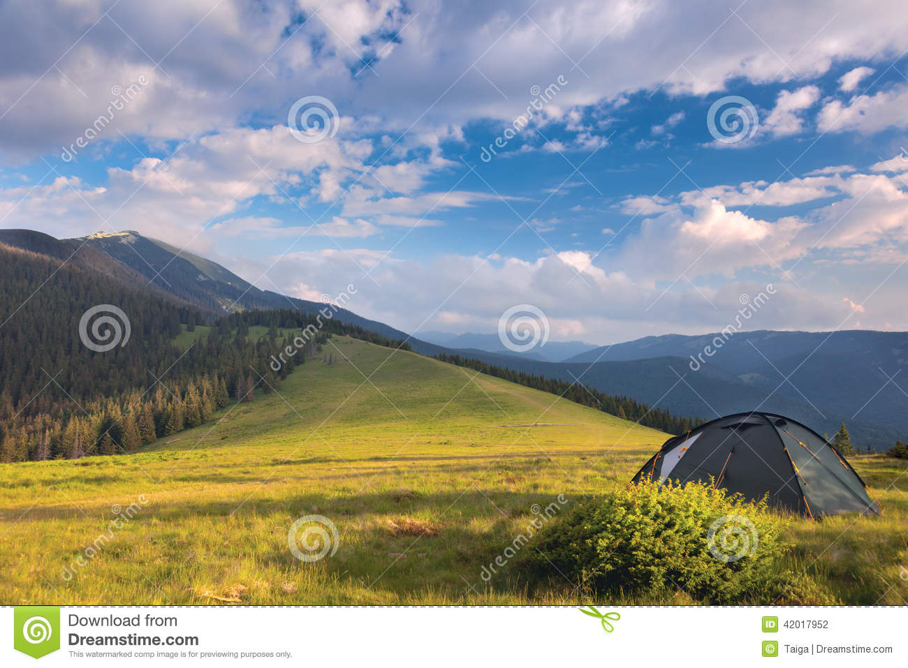 Camping tent in the mountains. Summer, blue sky, clouds and high