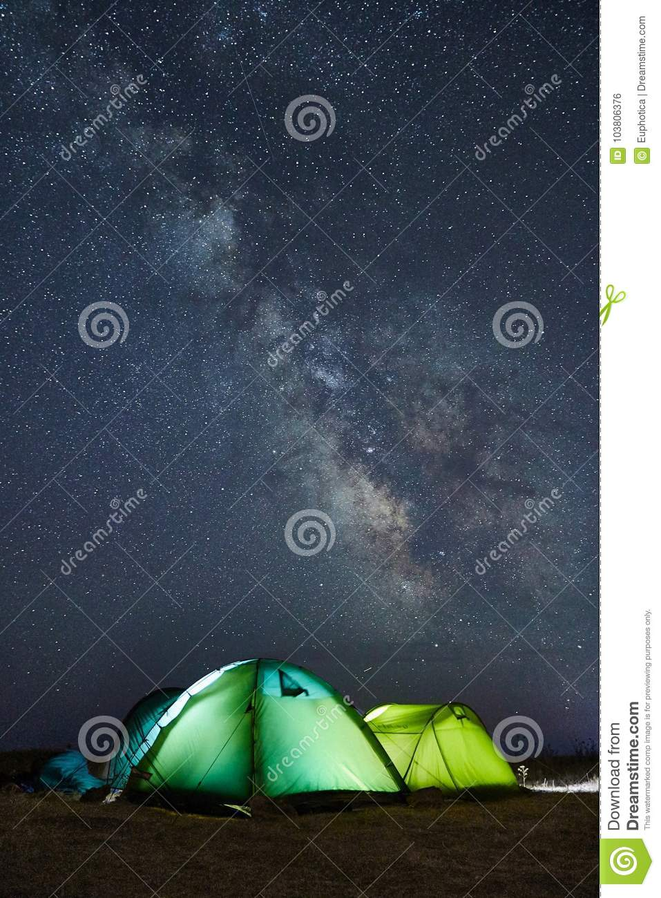 Camping under the stars with green illuminated tents, visible Milky Way galaxy, clear sky, long exposure