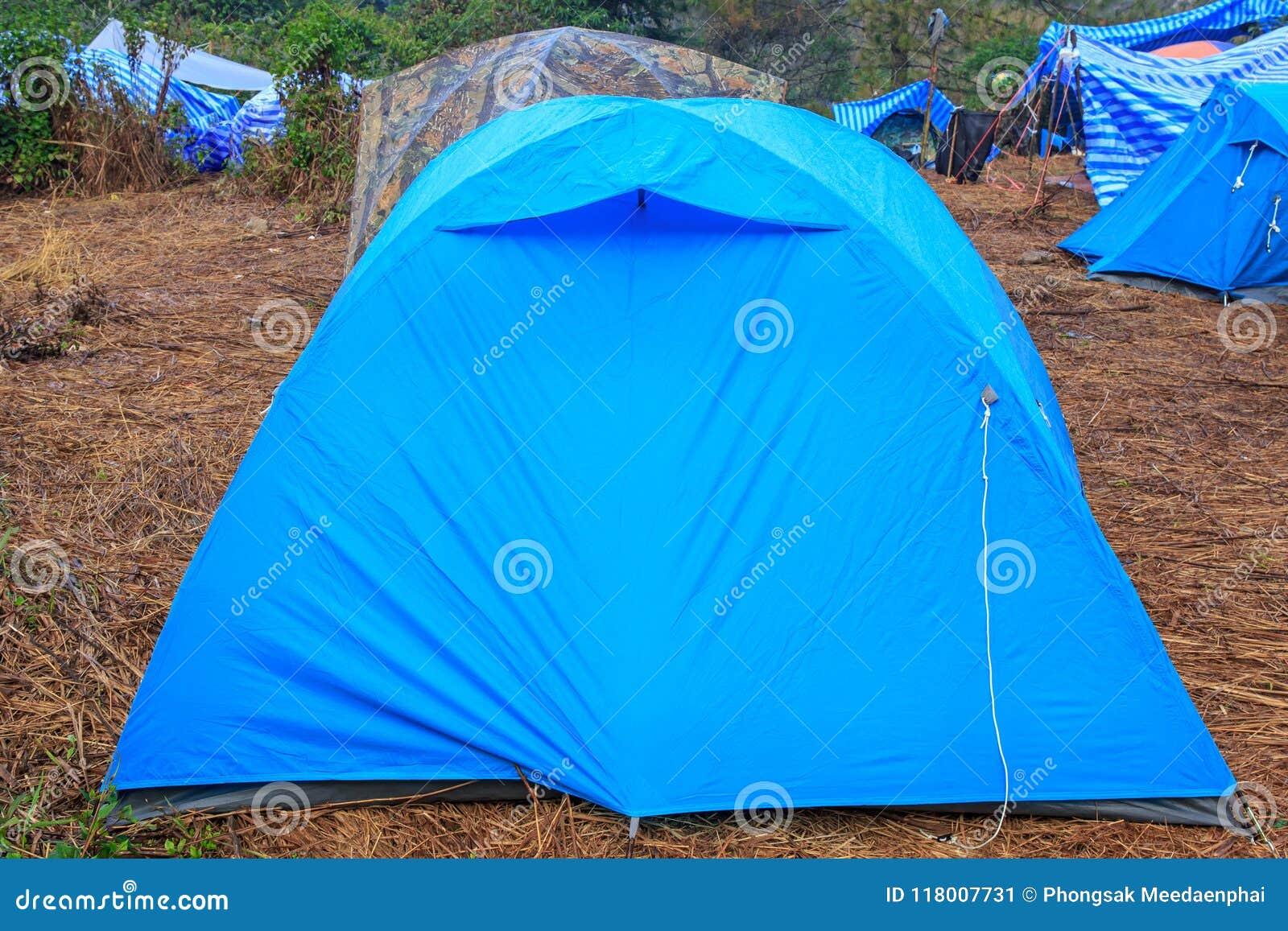 Campingowy namiot na suchej trawie blisko góry w ranku