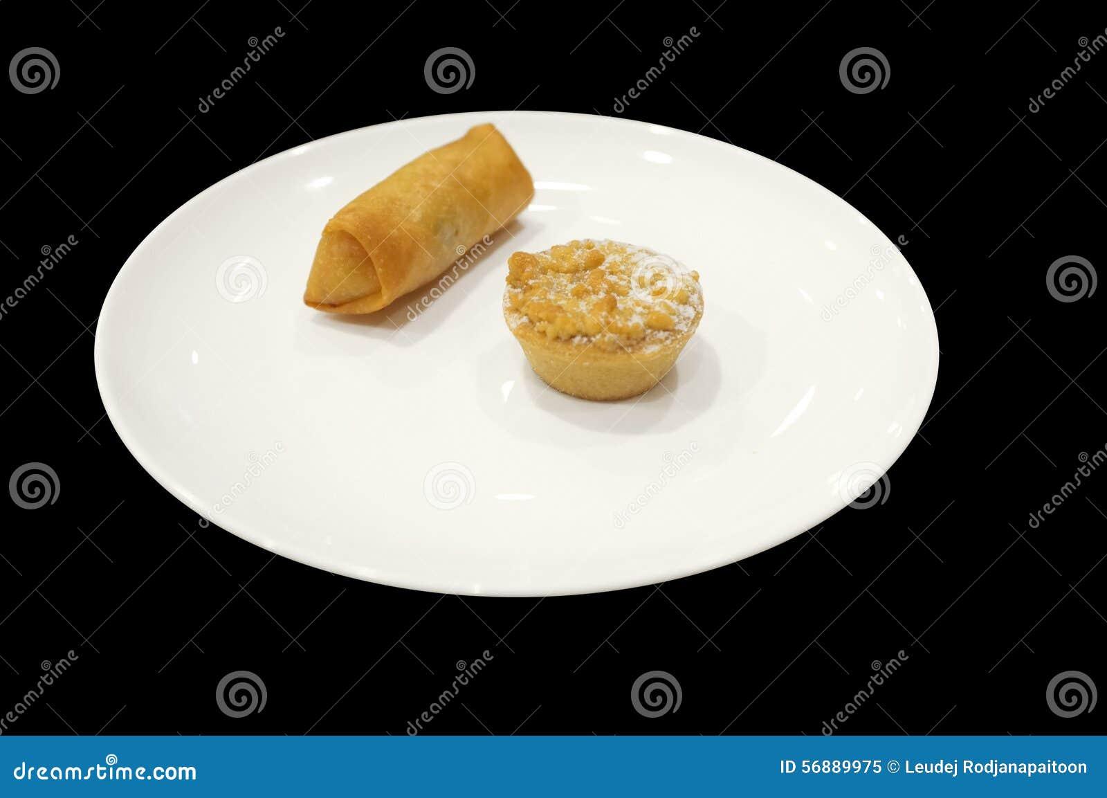 Campionatore dell aperitivo con il rotolo di molla e crostata sul piatto bianco