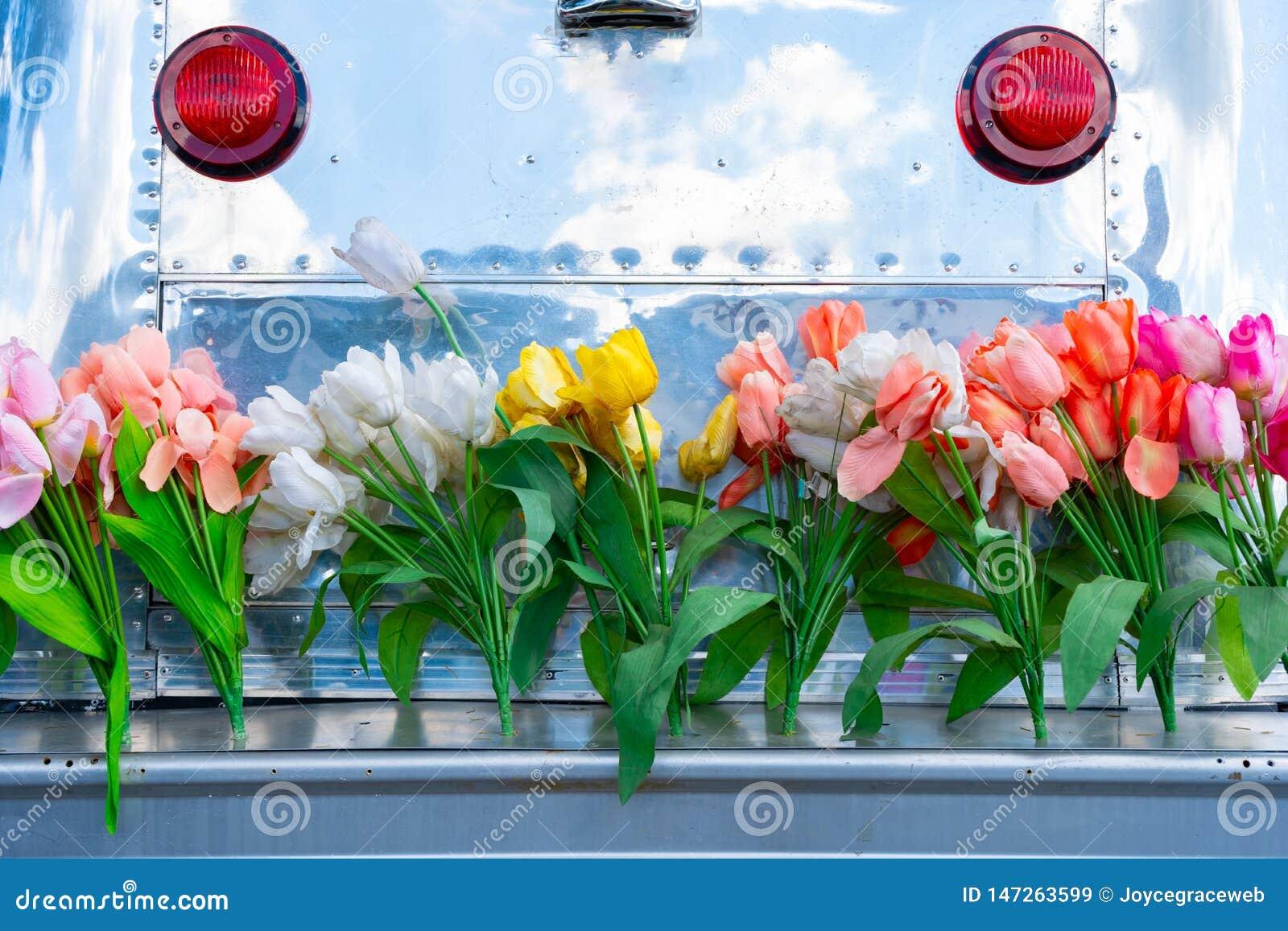 Campista do reboque do curso do vintage com tapume de alumínio e um amortecedor da bagageira coberto em flores da tulipa, descrev