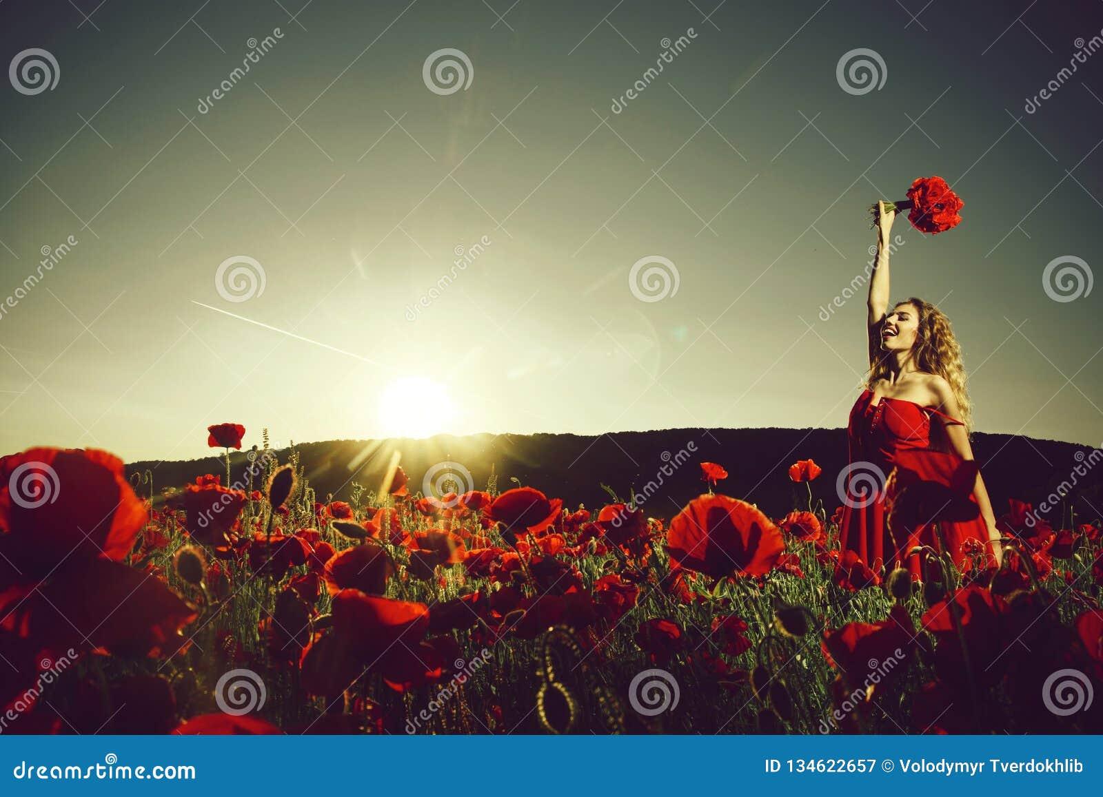 Campo da semente de papoila com mulher feliz