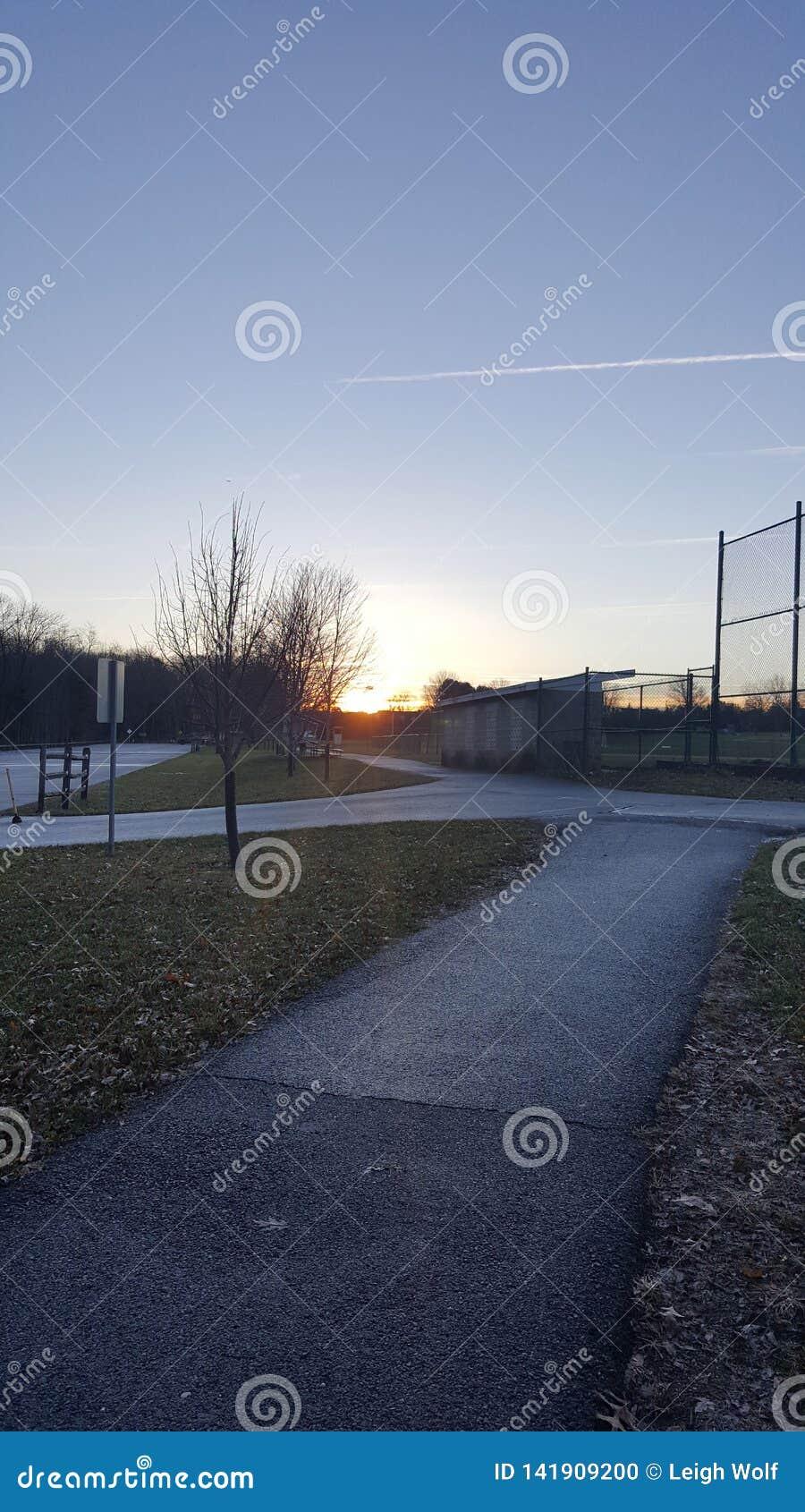 Campo de béisbol de la puesta del sol en un parque en el amanecer de la oscuridad