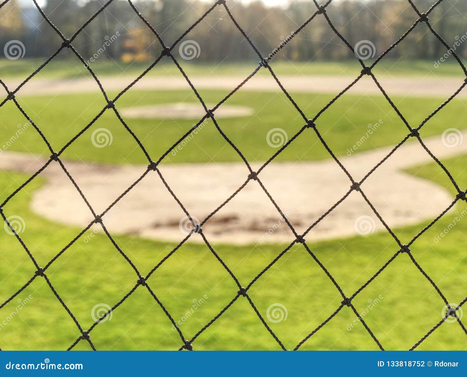 Campo de basebol da juventude visto da rede de trás