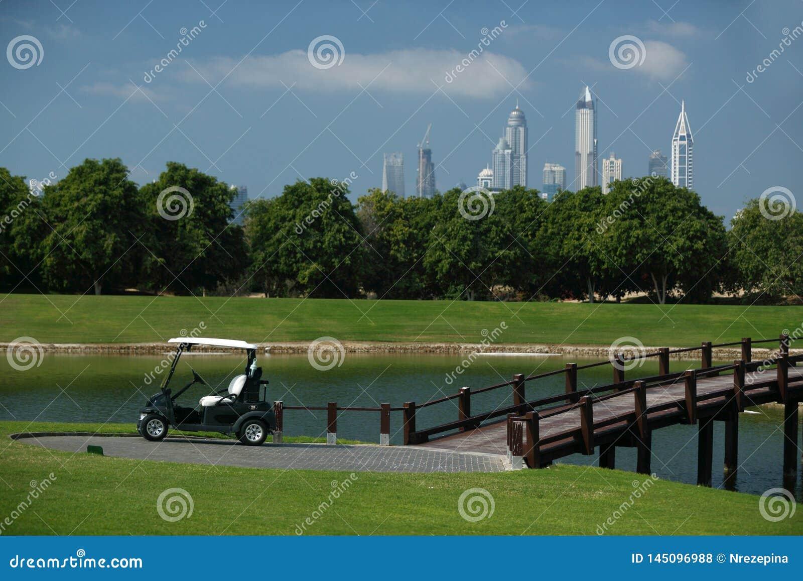 Campo de golf en Dubai con las palmeras y rascacielos en el fondo