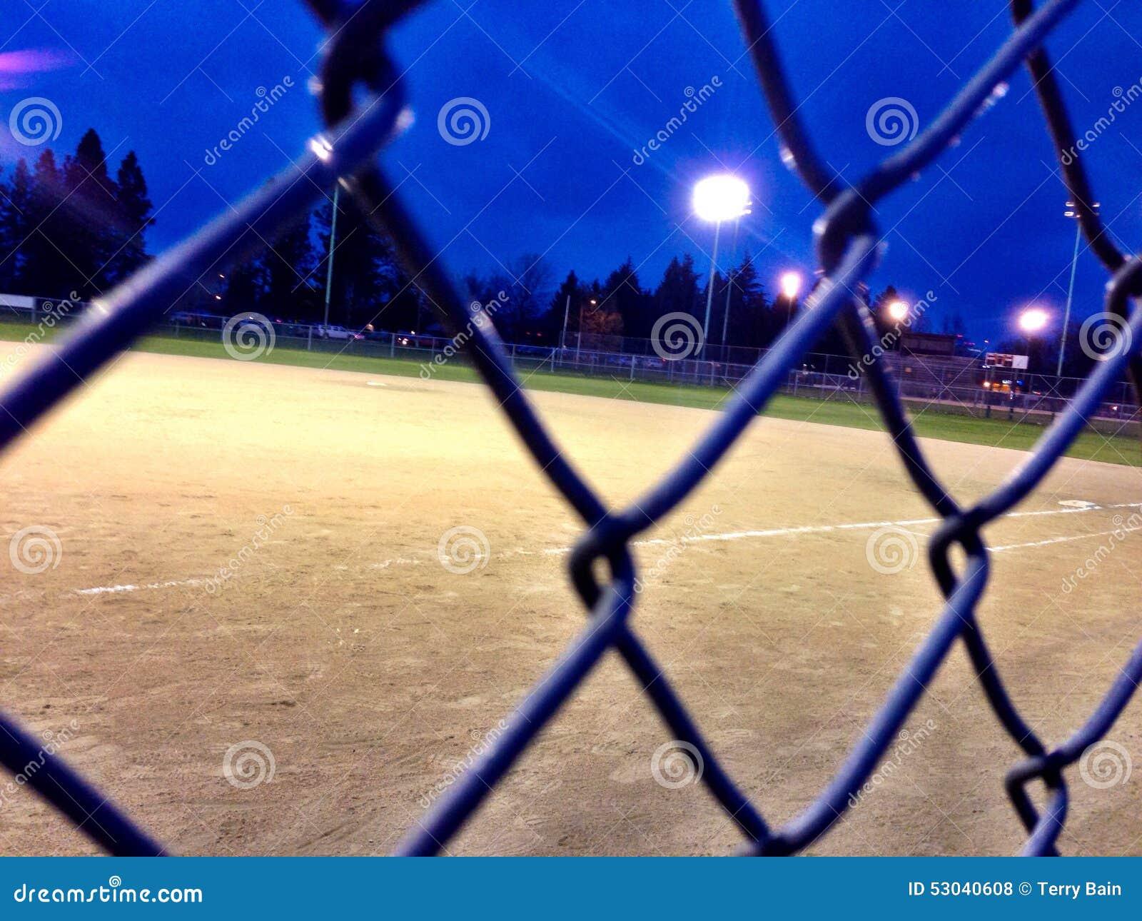 Campo e recinto di baseball alla notte nell ambito delle luci