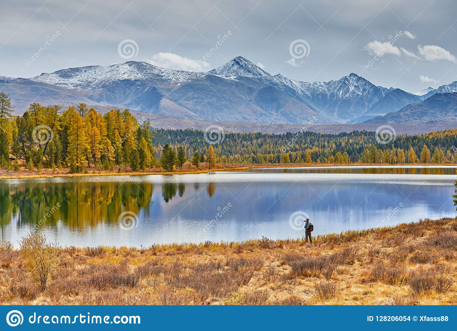 Campo en las montañas por el lago Paisaje hermoso del otoño El fotógrafo camina a lo largo de la orilla y hace tiros de