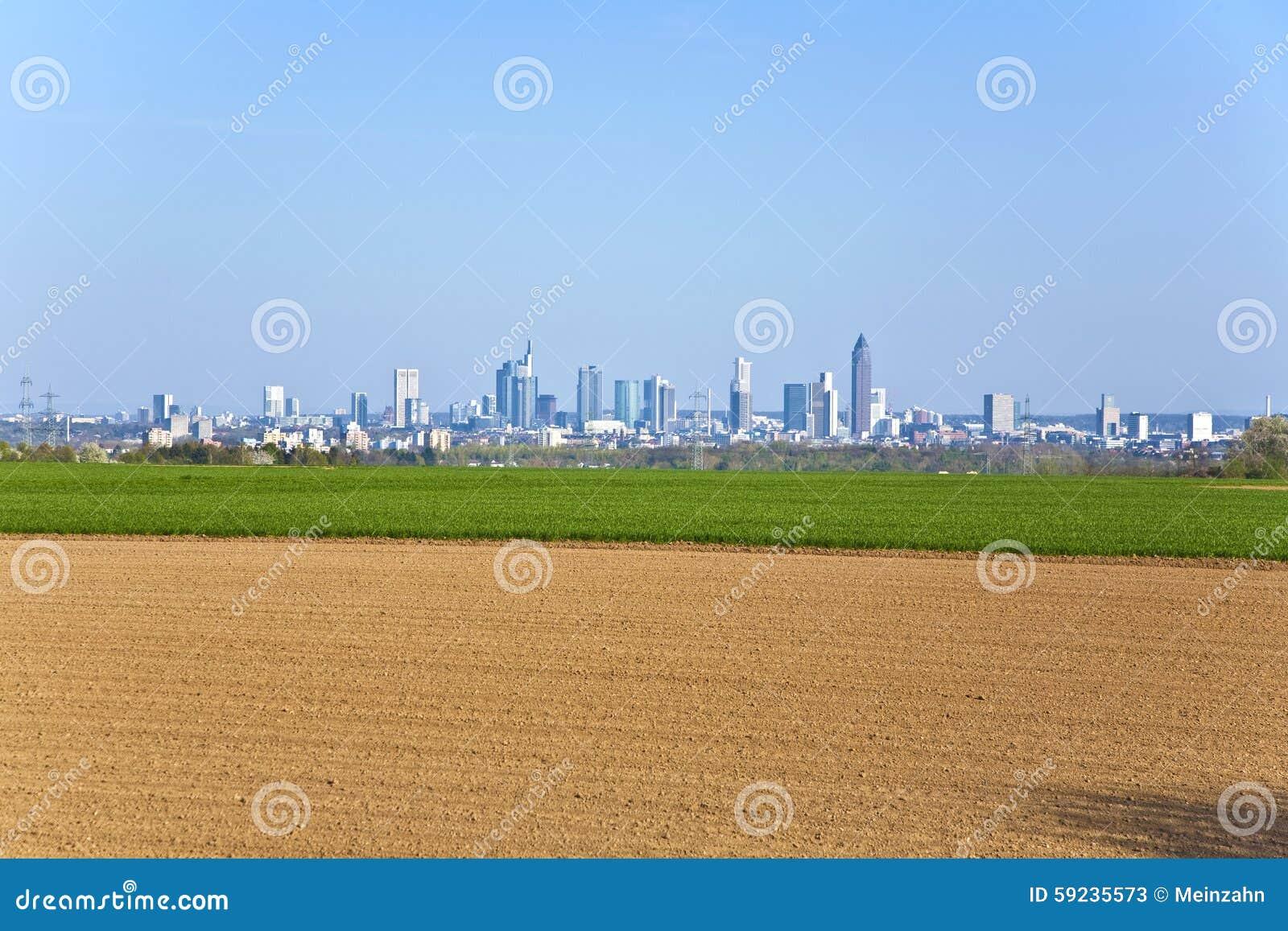 Campo recientemente arado con el paisaje urbano de Francfort en el horizo