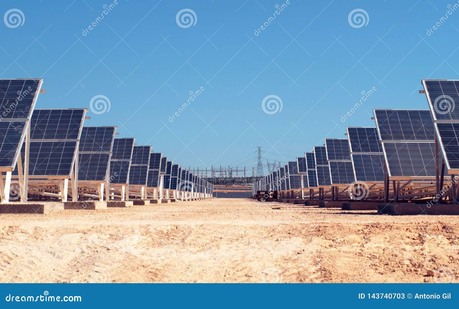 Campo solar con la estación de la energía eléctrica en el fondo