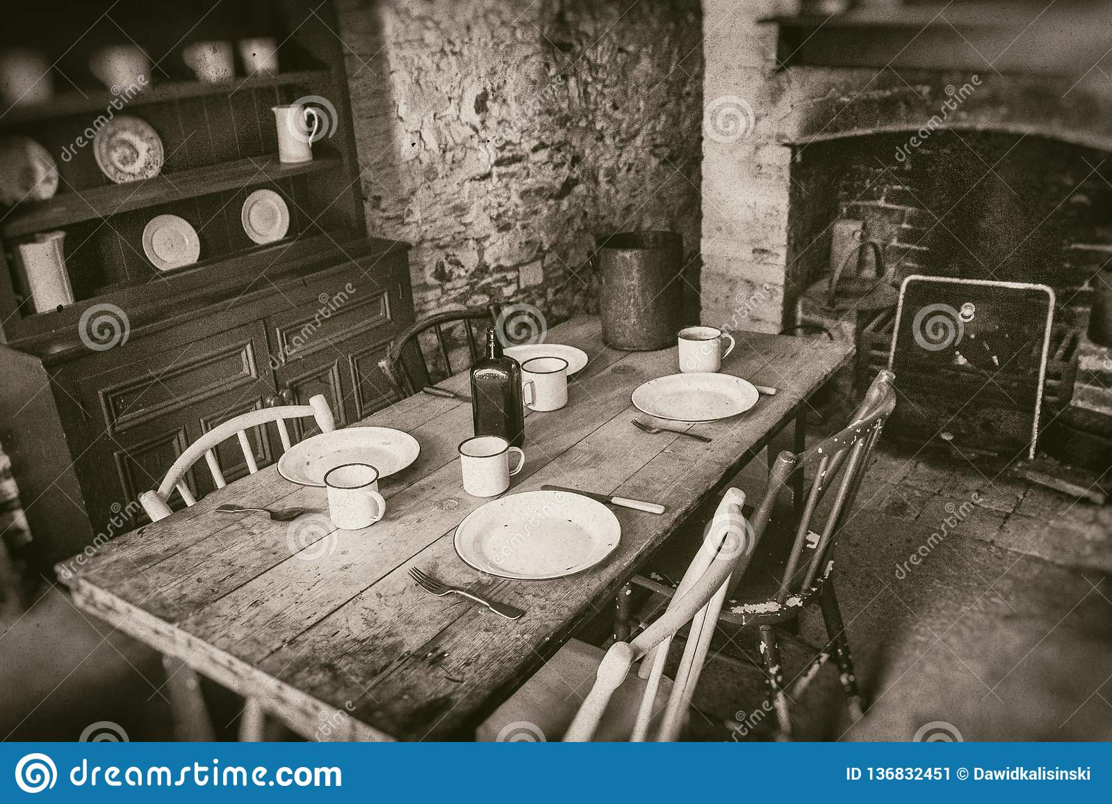 Camponeses pobres interiores do século XIX, da sala de jantar com a tabela de madeira ajustada e da chaminé, fotografia do estilo