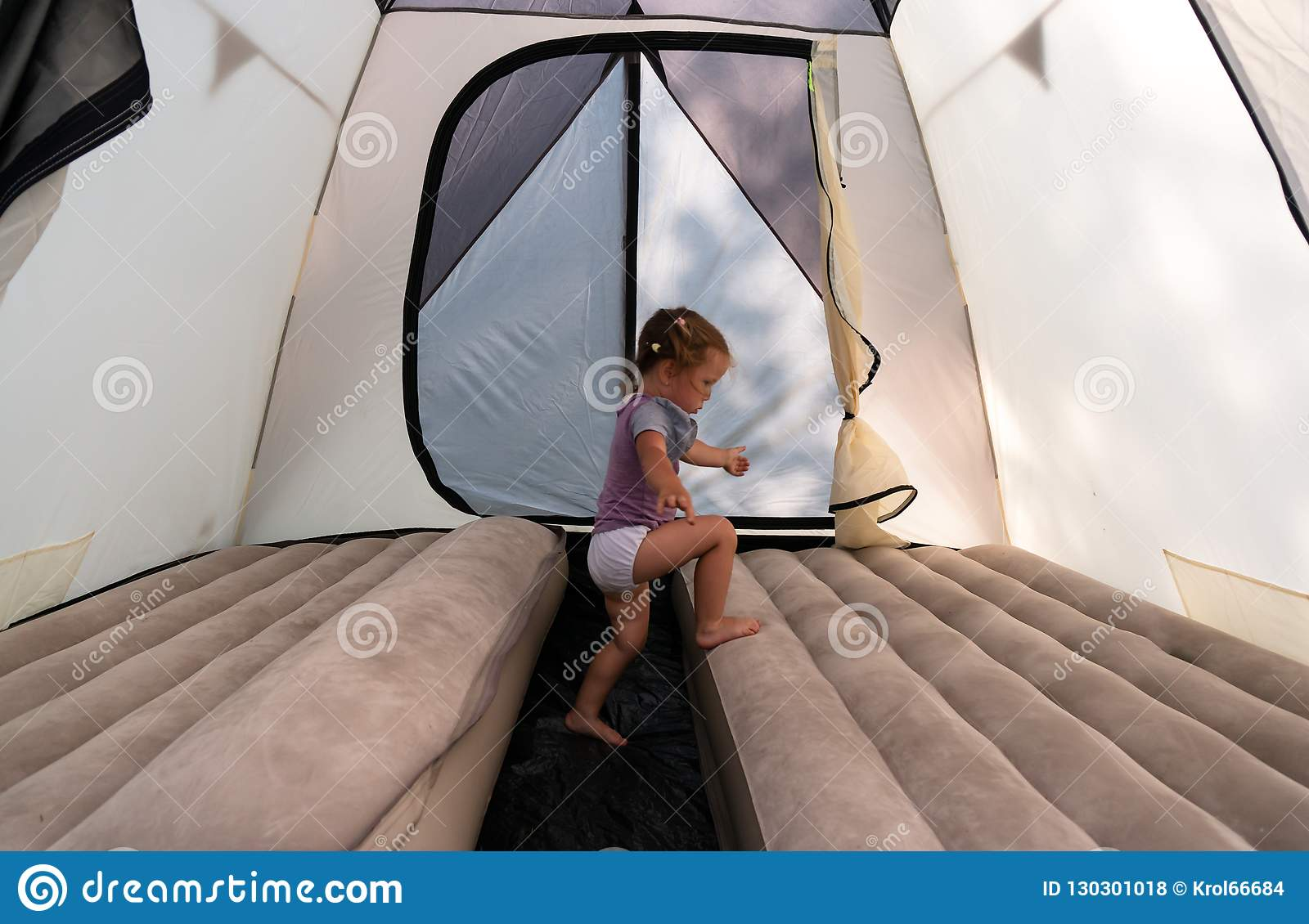 At the campsite, a little girl in a tent jumps on mattresses.