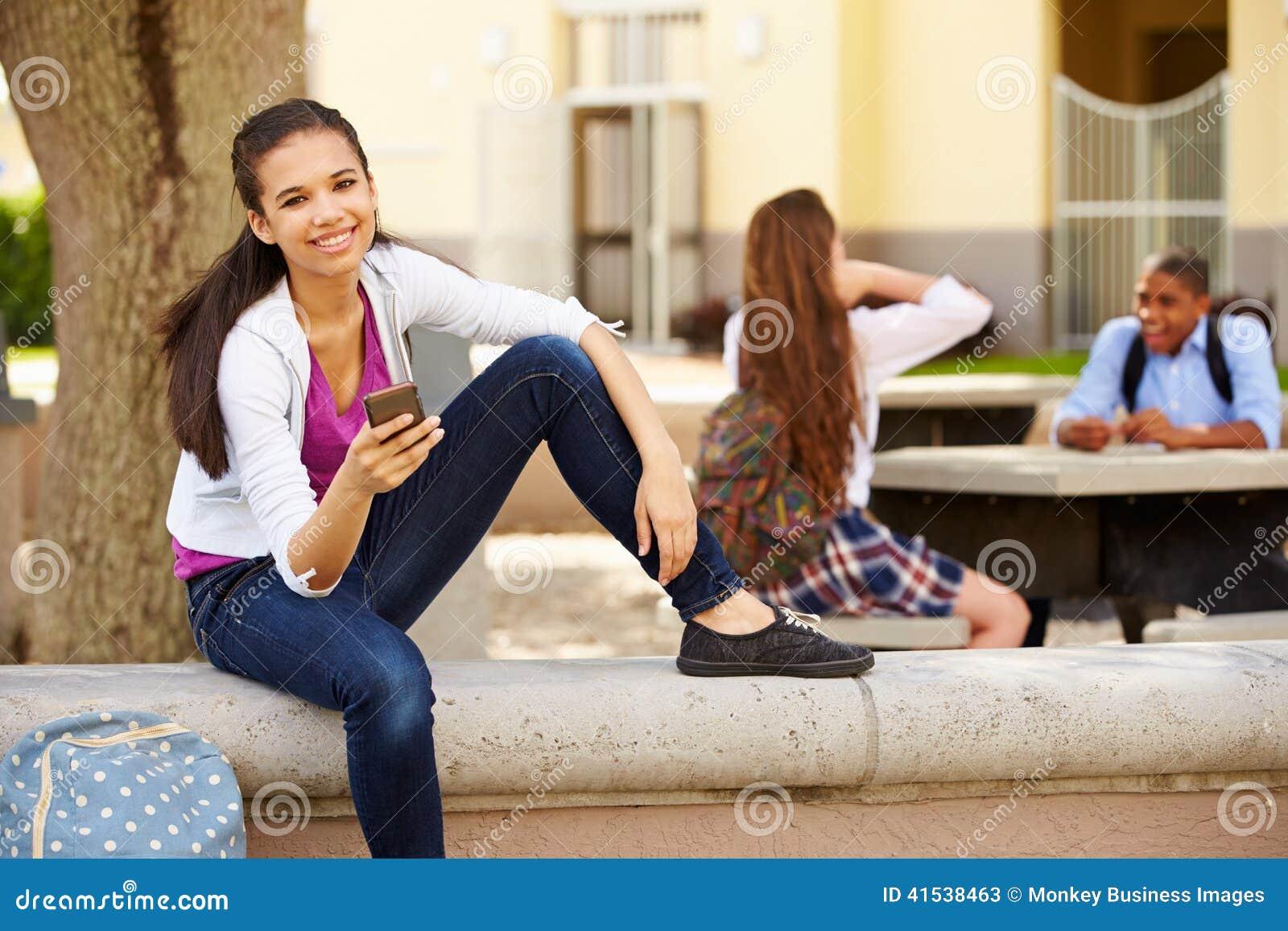 Campus femelle d école d Using Phone On d étudiant de lycée